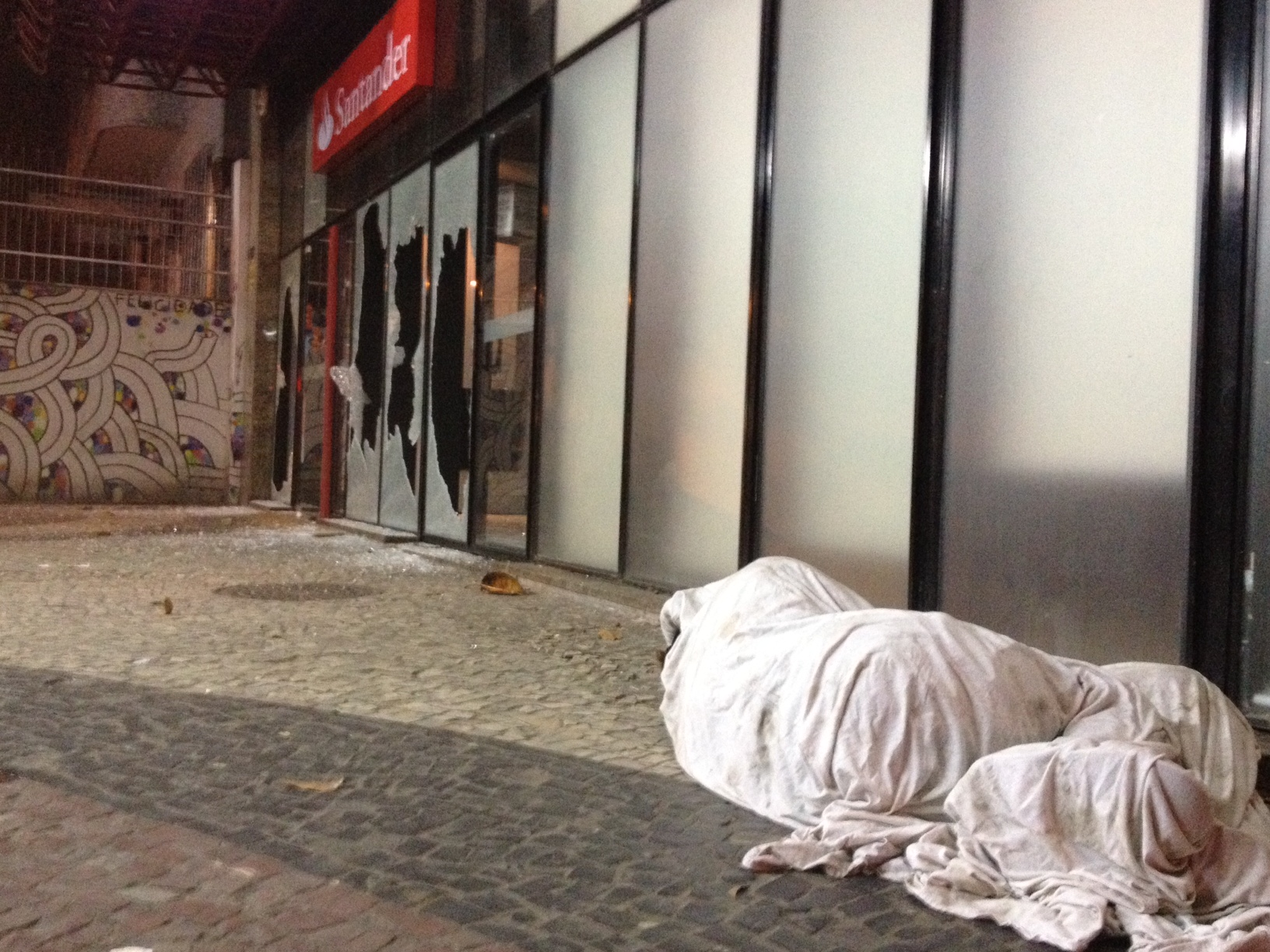 Mendigo dorme em rua onde banco teve vidraças quebradas