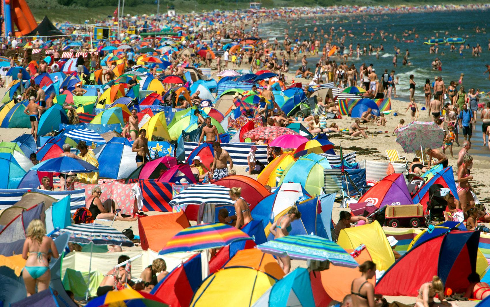 Banhistas aproveitam dia de calor e sol na praia de Zinnowitz, na Alemanha; a praia fica localizada no Mar Báltico