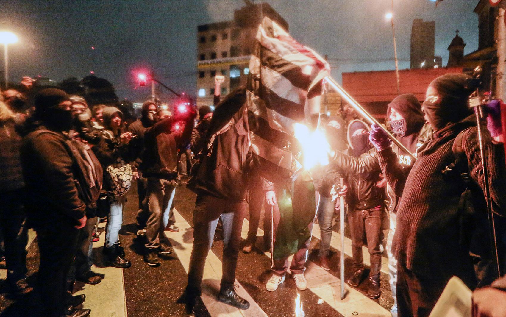 Encapuzados queimam bandeira do estado de São Paulo durante ato em SP
