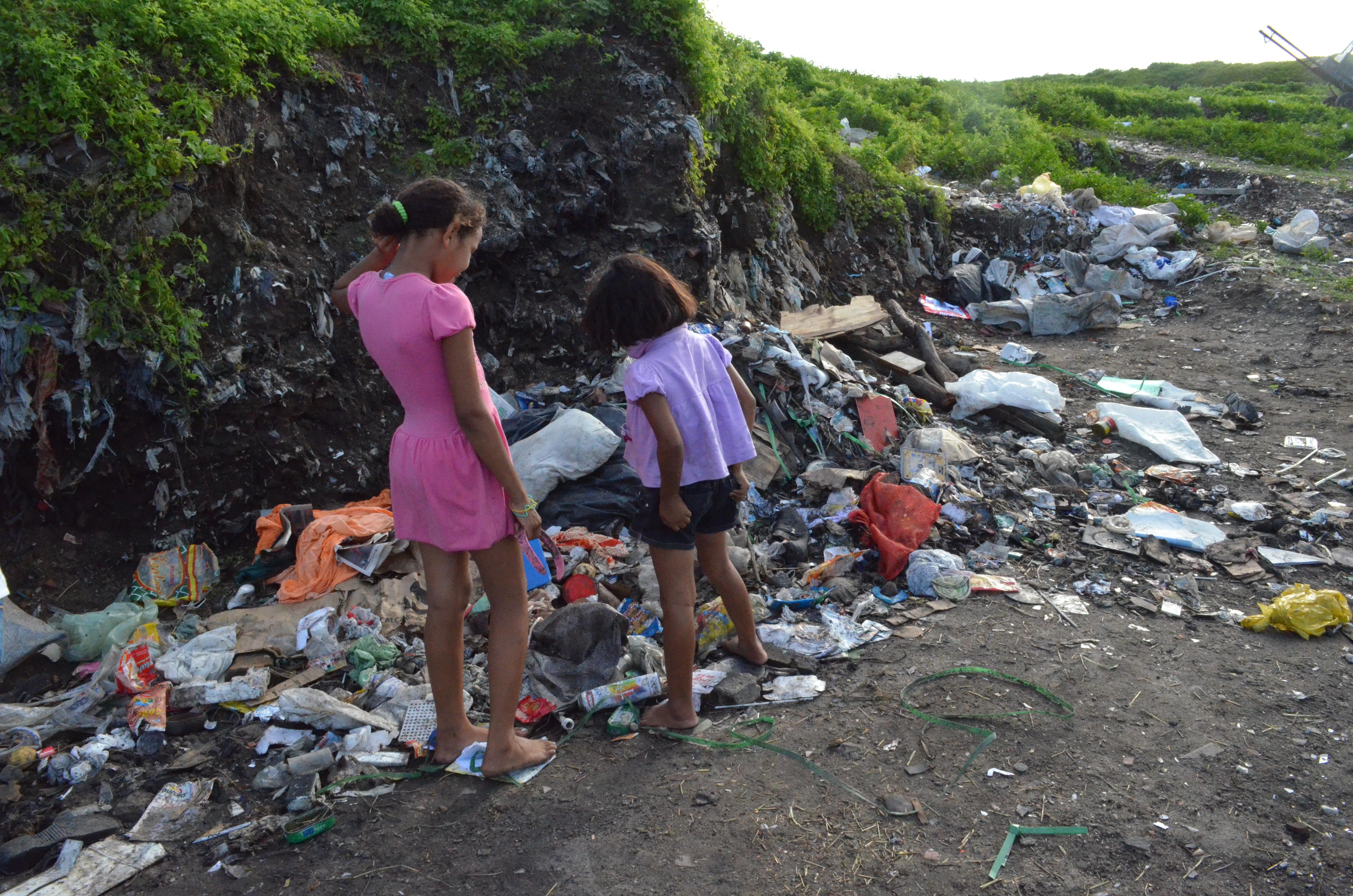 Meninas brincam em meio ao lixo, que ainda é visível, no Lixão do Roger, em João Pessoa.