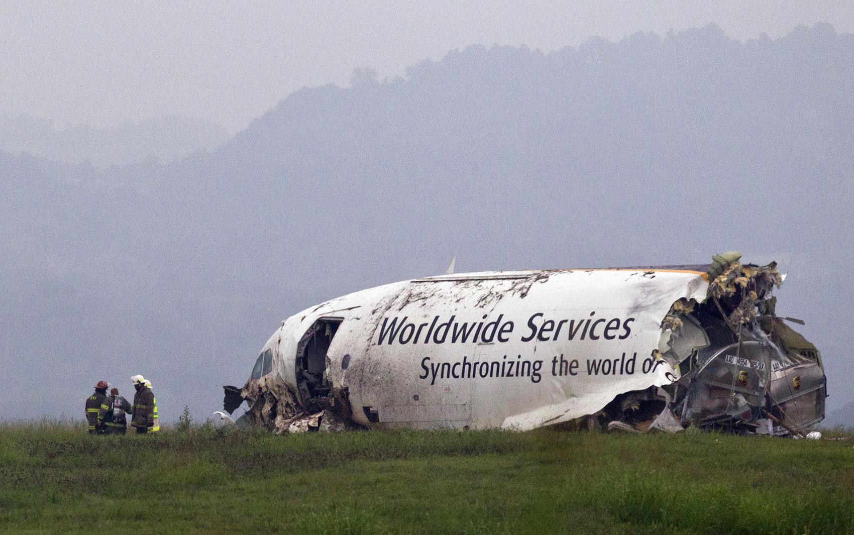 Bombeiros trabalham em frente à carcaça da parte frontal do avião acidentado no Alabama