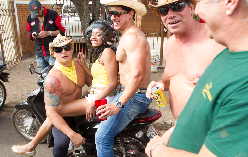 O gogo boy André Maia, de lenço amarelo, para mulher que passava de moto em frente à república que alugou com os amigos