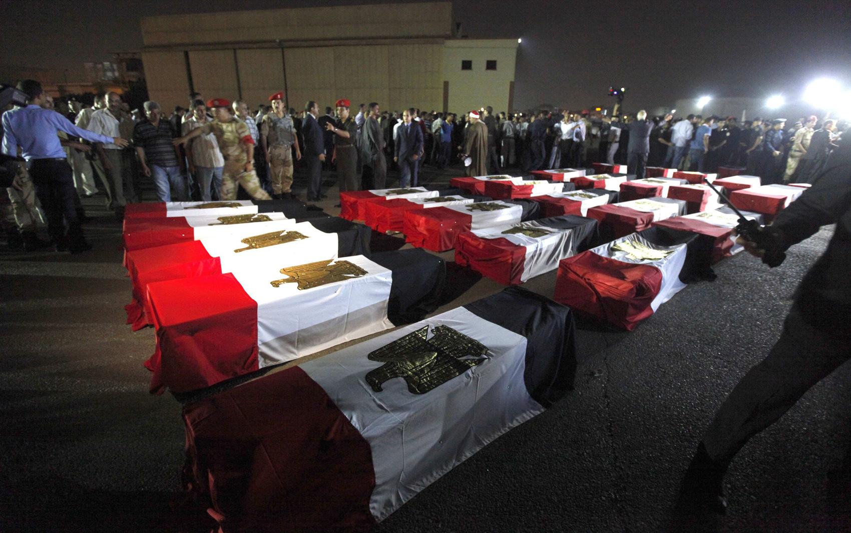 19/8 - Caixões de 25 policiais mortos na manhã de segunda-feira (19) perto da cidade de Rafah chegam ao aeroporto militar de Almaza no Cairo.