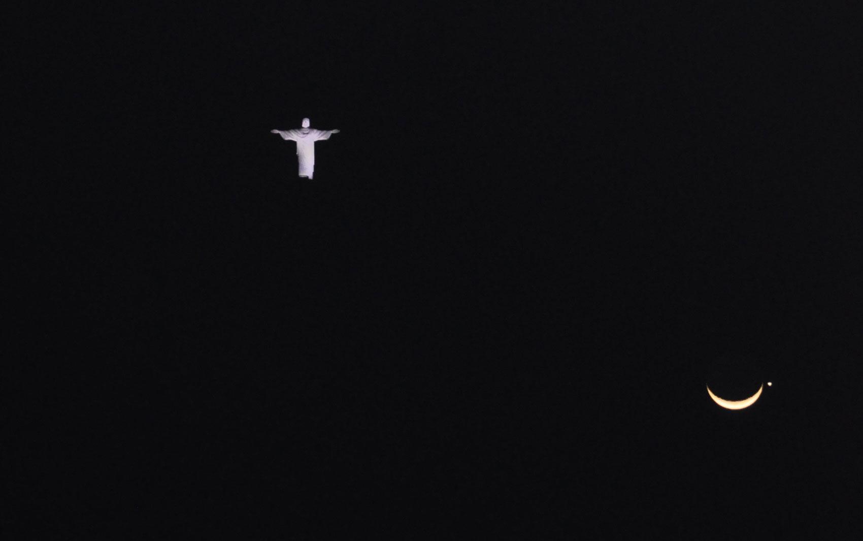 O Cristo Redentor parece flutuar no céu junto com a lua nesta foto da internauta Rebeca Machado, do Rio de Janeiro