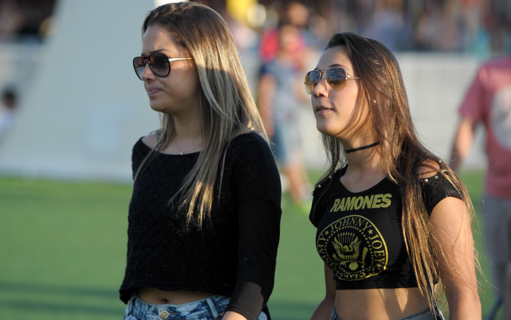 Jovens caminham pela Cidade do Rock neste domingo (15), uma delas com camiseta dos Ramones