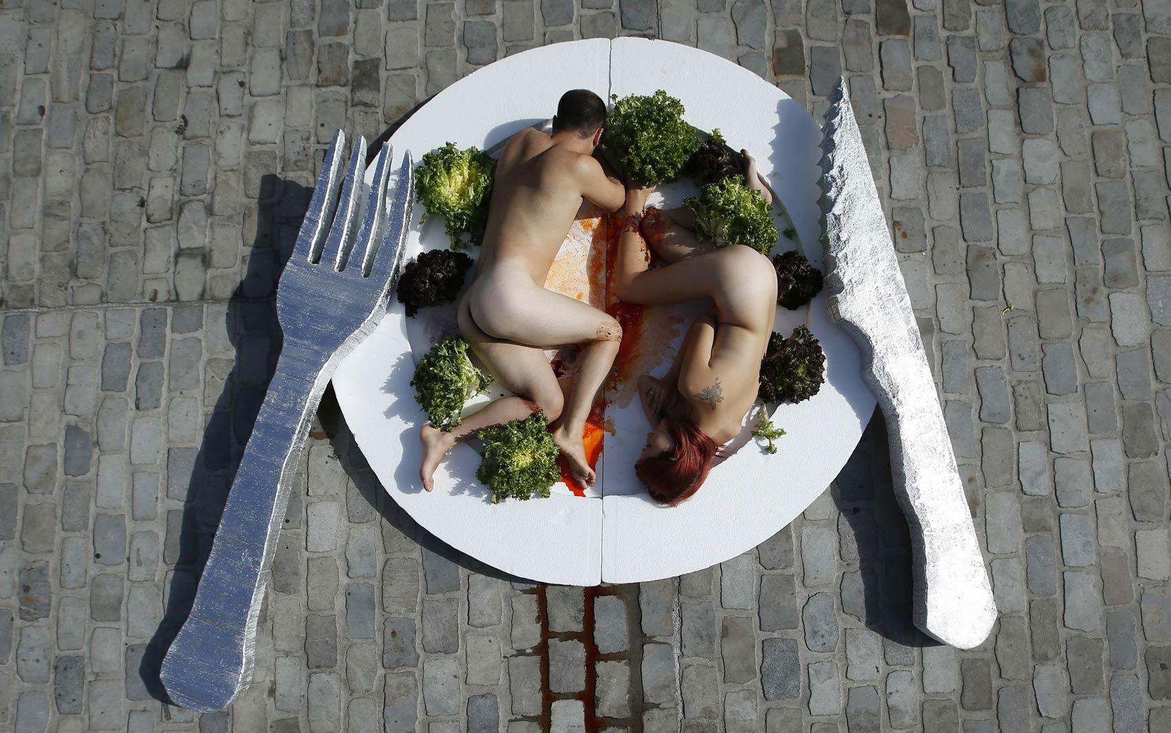 Casal 'se serve' nu em um prato gigante em protesto promovendo o vegetarianismo no centro de Barcelona, na Espanha.