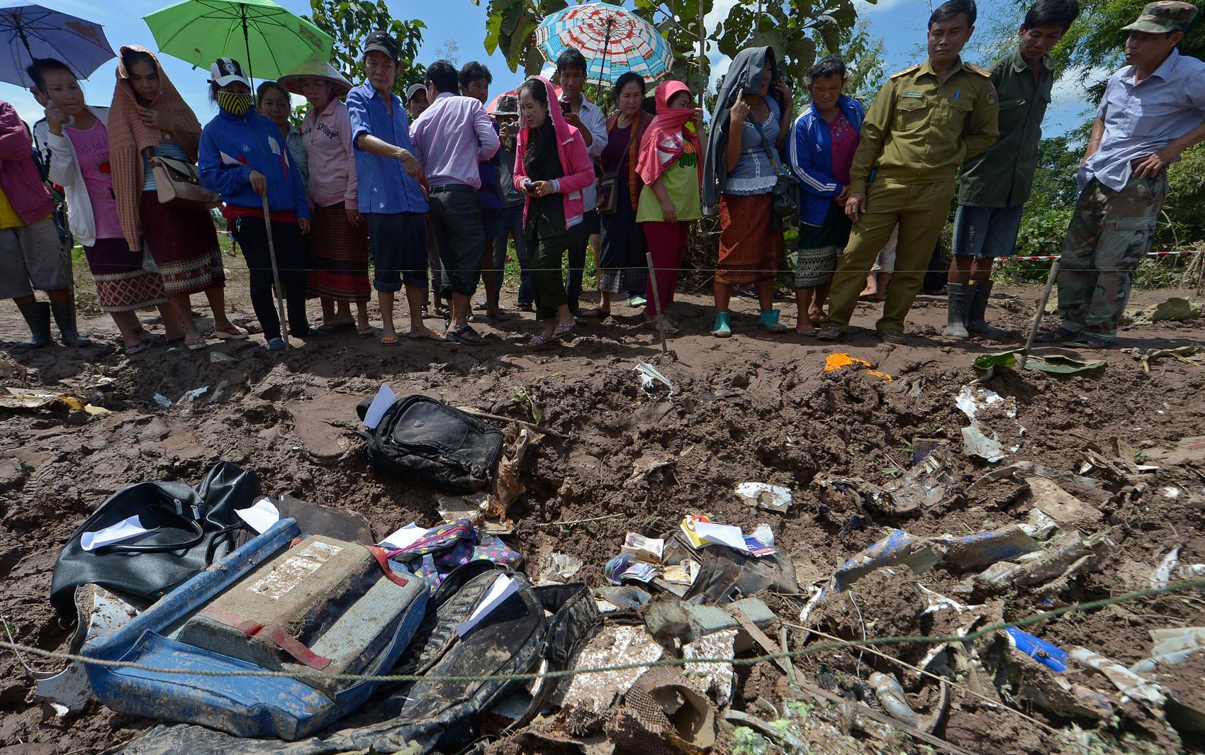Moradores observam nesta quinta-feira (17) destroços do avião acidentado no Rio Mekong, no Laos