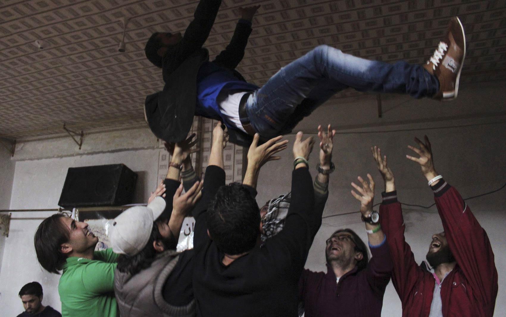 25/10 - Combatentes do Exército Livre da Síria jogam para cima um colega rebelde durante a festa do seu casamento em Salaheddine, em Aleppo
