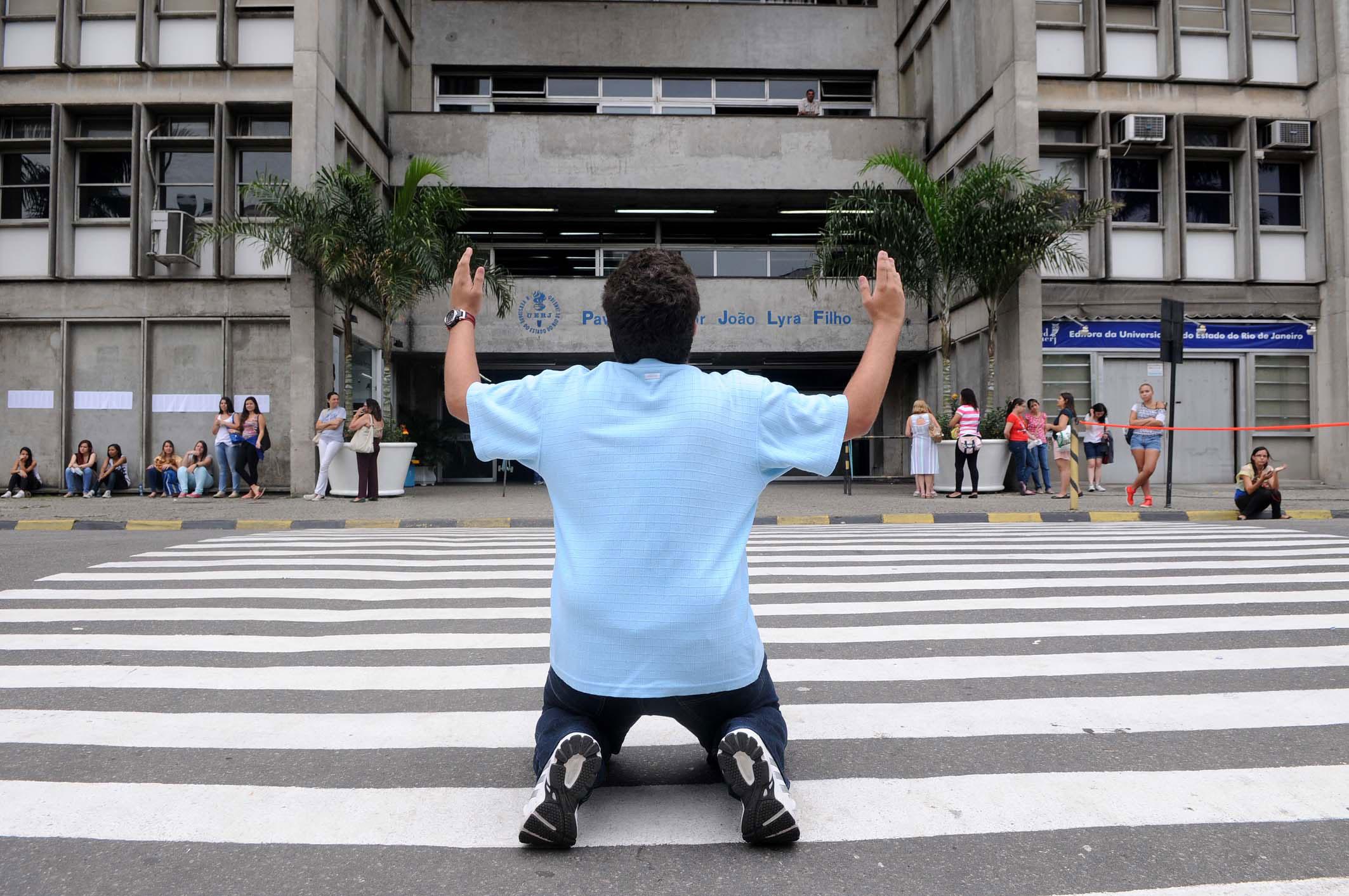DOMINGO (27): Rio de Janeiro (RJ) - Candidato se ajoelha em frente ao local de prova, na Uerj.