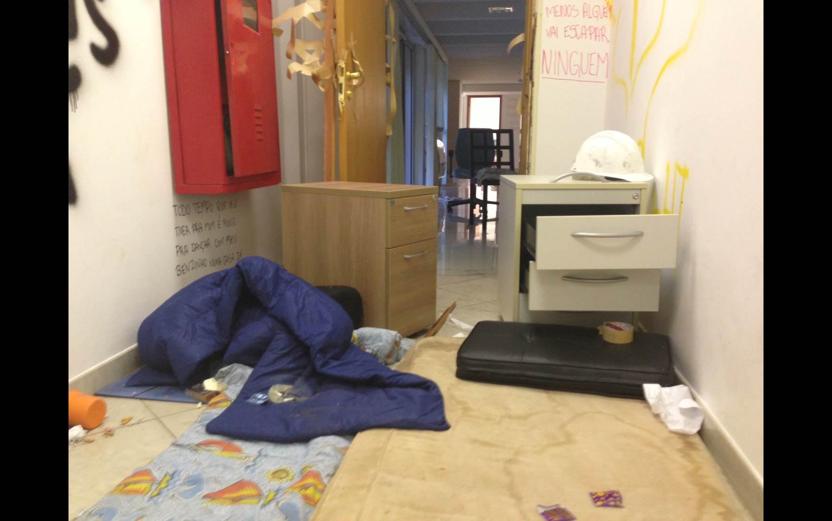 Pacotes de camisinha são vistos sobre colchões e coberta em um quarto da Reitoria que teve paredes pichadas