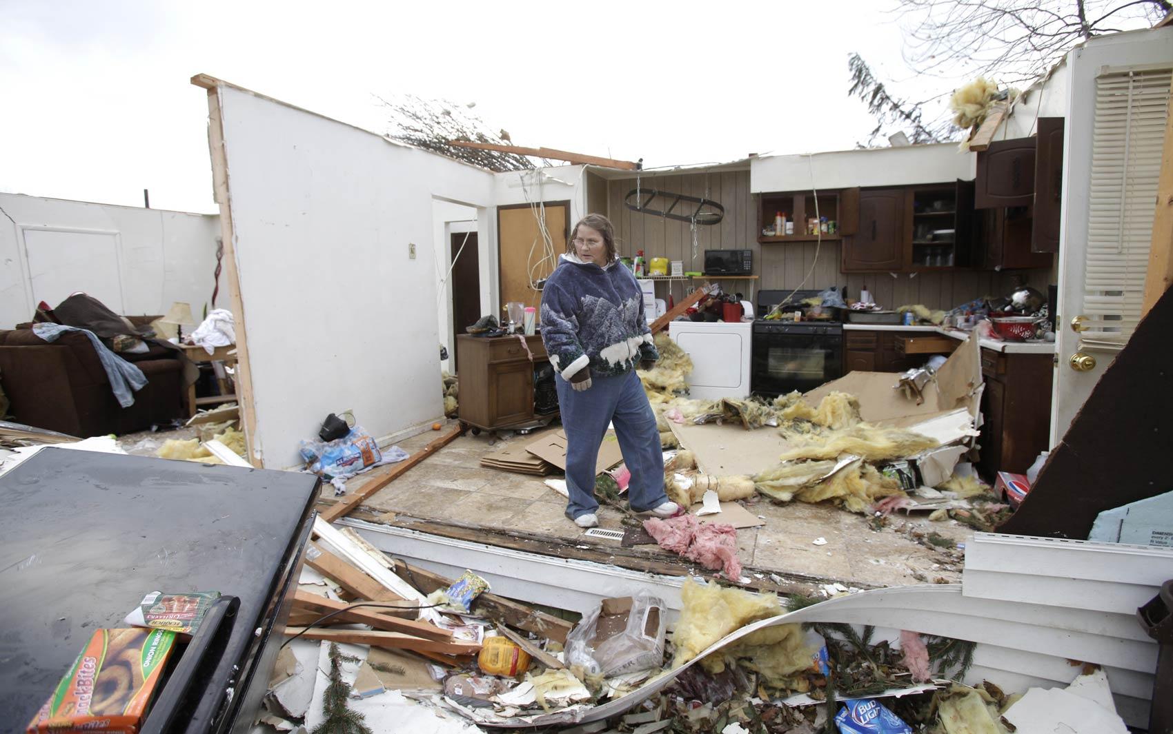 Mulher caminha na cozinha destruída pelo tornado que atingiu a casa de seu filho em Jerry City, Ohio, nesta segunda (18)