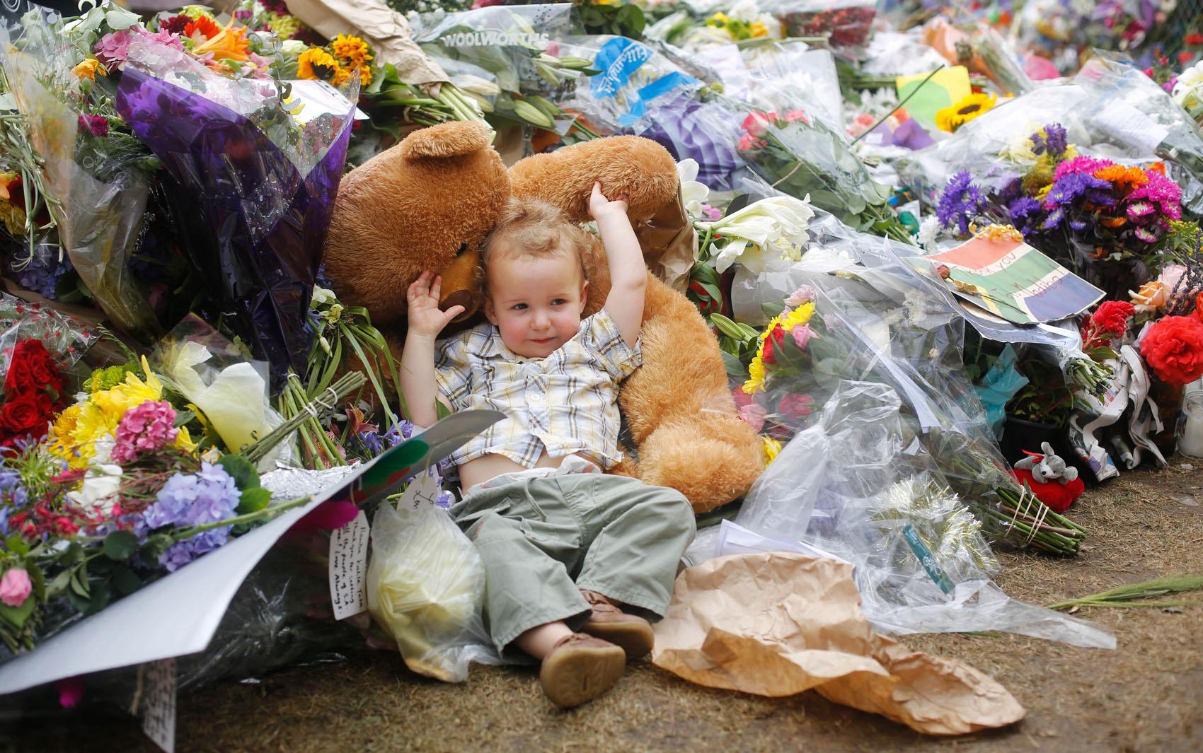 9/12 - Criança deita em urso de pelúcia deixado em memorial na frente da casa do ex-presidente Sul-Africano Nelson Mandela, em Joanesburgo.