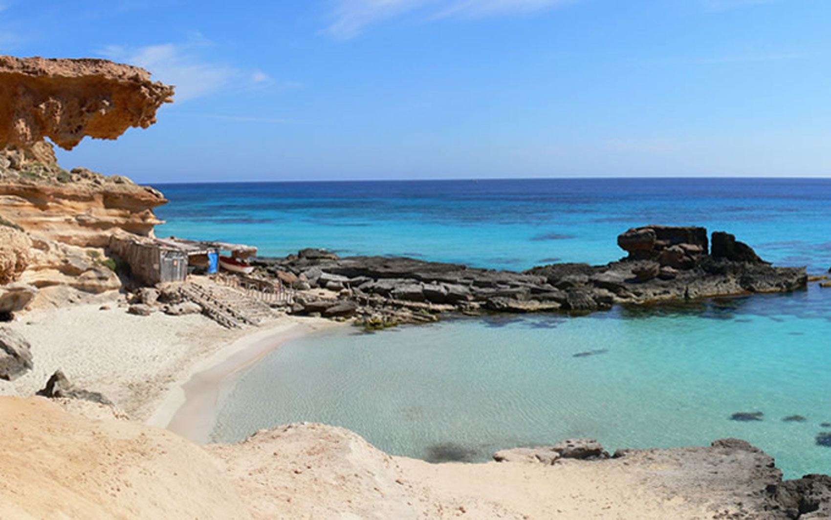 Praia de areia branca e mar azul em Ibiza, ilha que fica no leste da Espanha