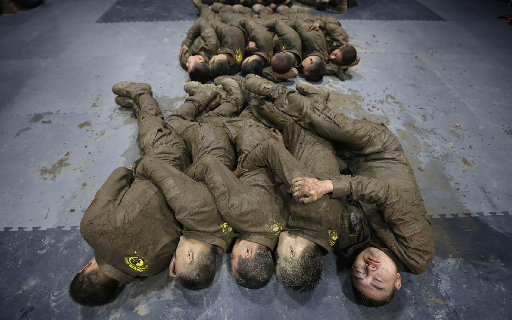 Sujos de lama, estudantes chineses dormem de 'conchinha' para evitar o frio durante treinamento de alta intensidade no acampamento Tianjiao de Guarda Especial e Consultoria de Segurança, perto de Pequim, China. O curso prepara guarda-costas profissionais.