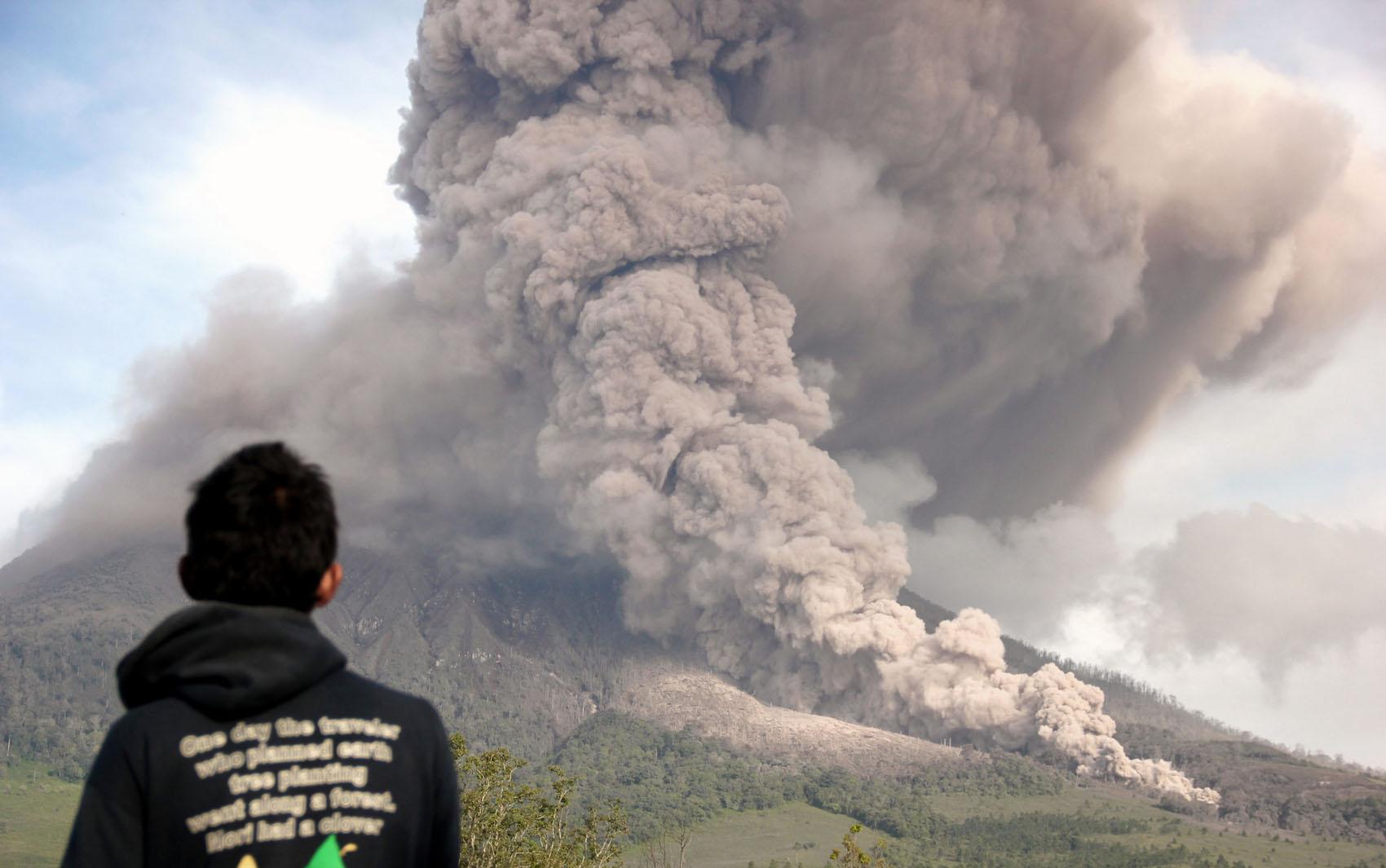 Homem observa o Monte Sinabung durante erupção no norte de Sumatra, na Indonésia.