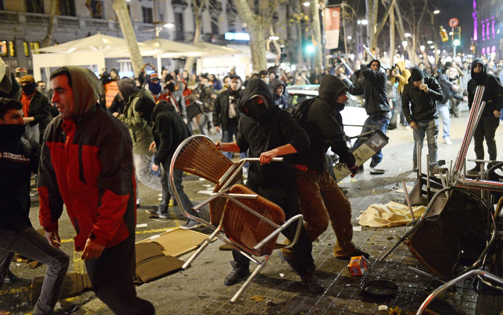 Manifestantes entram em confronto com a polícia em Barcelona durante um protesto em apoio aos moradores do bairro Gamonal na cidade de Burgos, que são contra um projeto de renovação urbana com valores altos para o país em crise.