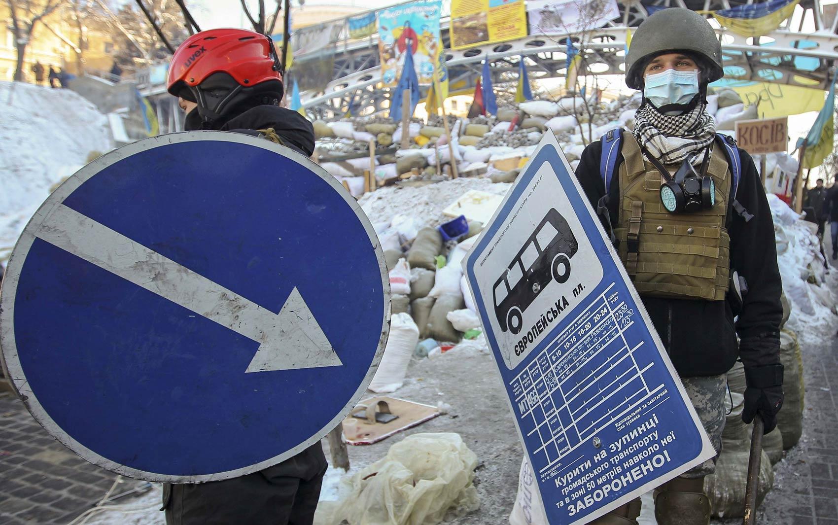 Manifestantes ucranianos usam placas de trânsito como escudos improvisados ao lado de uma barricada construída em rua do centro de Kiev