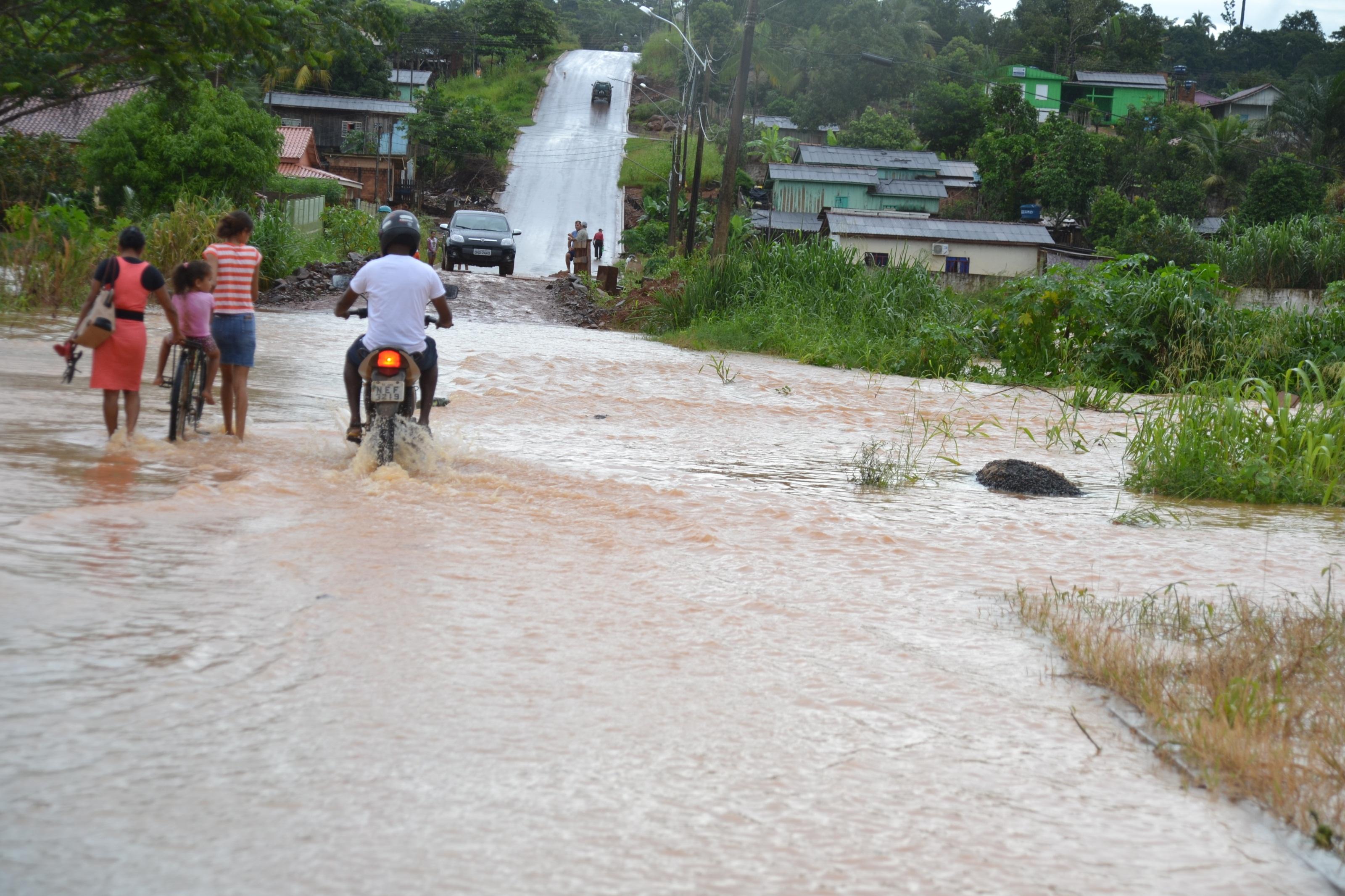 Moradores se arriscam a passar por vias alagadas em Jaru, RO