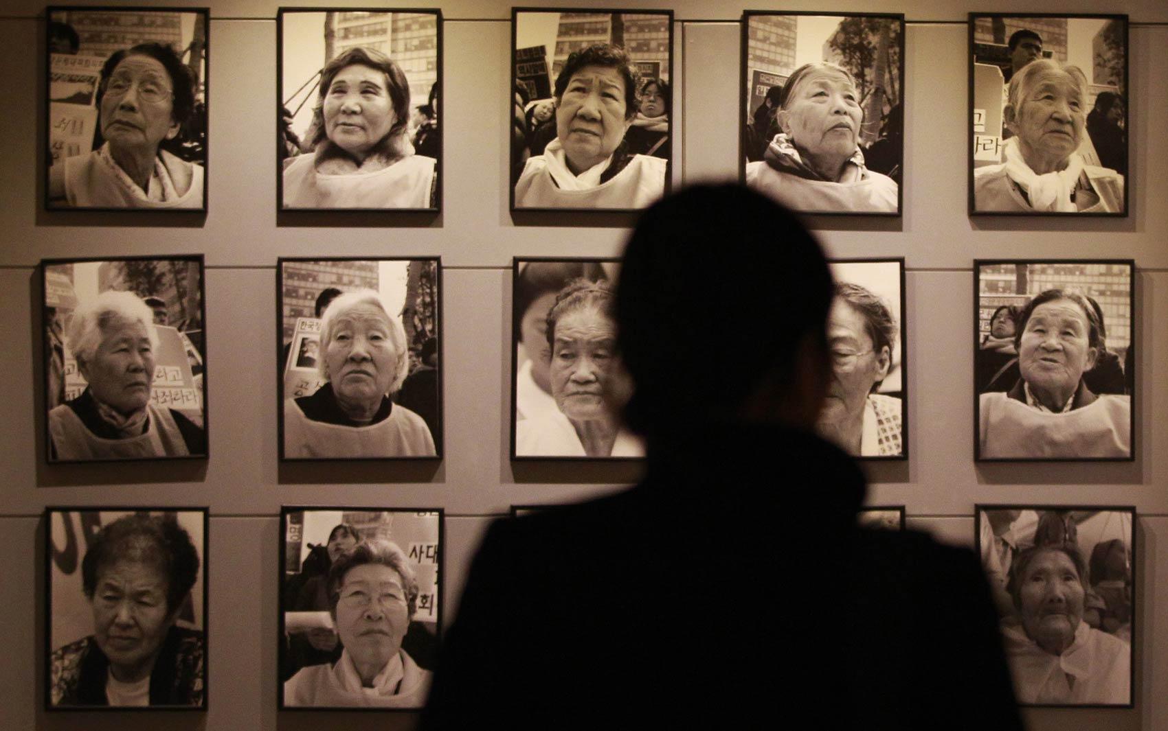 Visitante observa retratos de mulheres já falecidas que serviram como escravas sexuais de tropas japonesas durante a II Guerra Mundial, na 'Casa de Compartilhar'. O lar de idosos funciona como museu em Toechon, na Coreia do Sul.