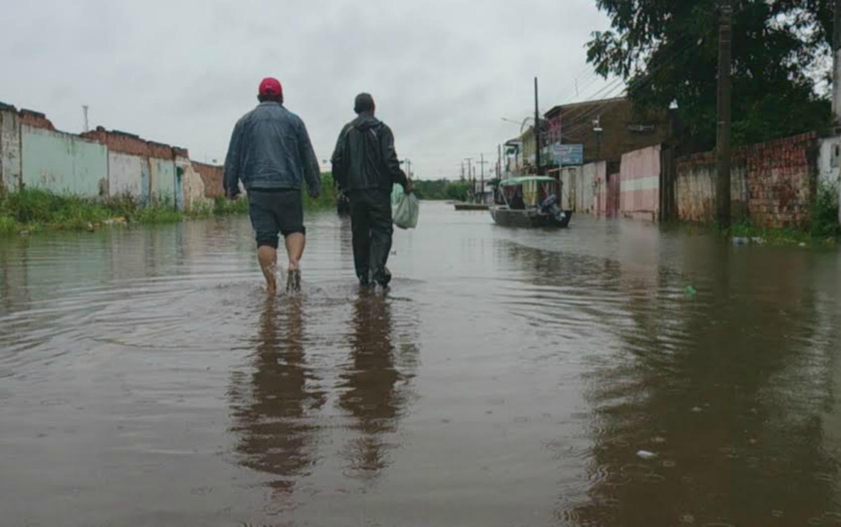 Moradores se arriscam ao atravessar rua tomada pela cheia do Rio Madeira