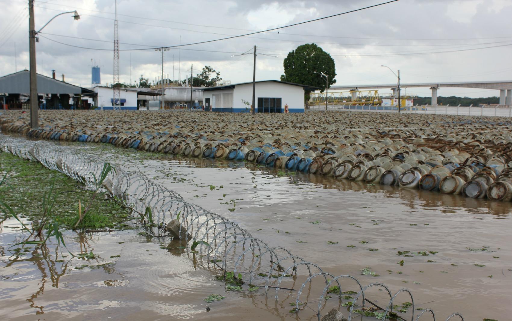 Botijões boiam em distribuidora de gás, após área ser tomada pela cheia do Rio Madeira