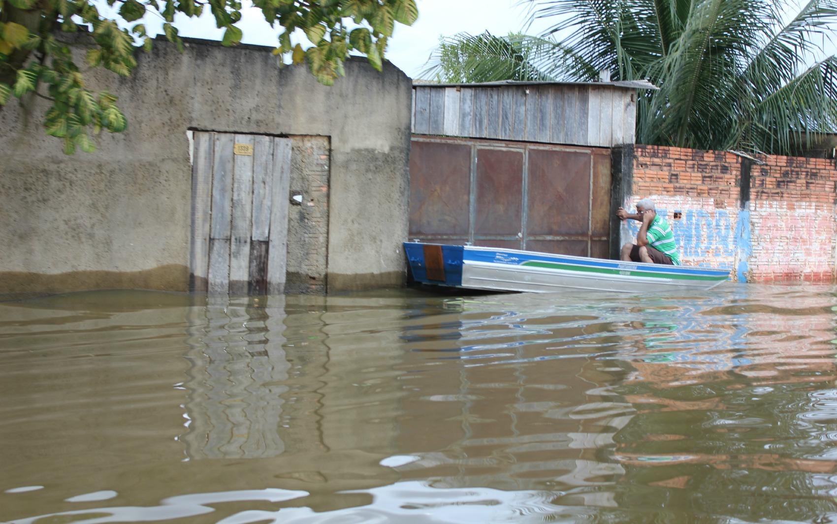 Moradores chegam de barco em suas casas no centro da capital