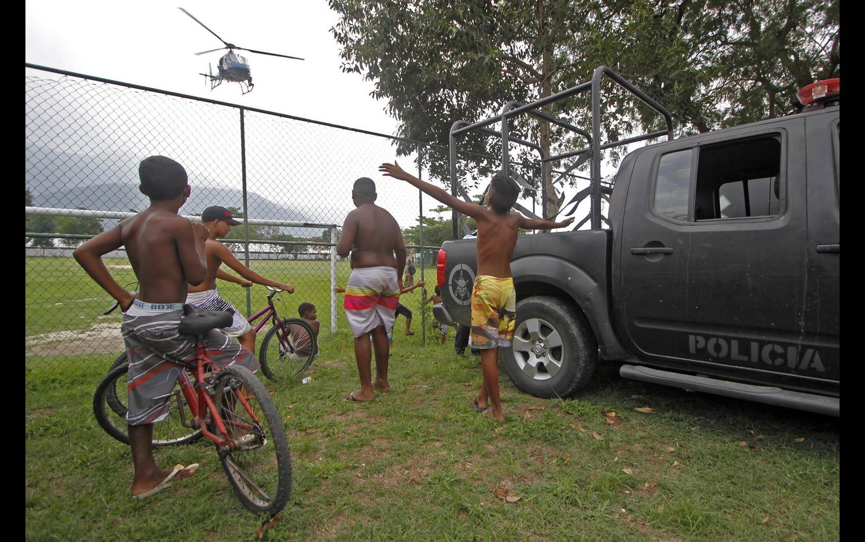Meninos observam a chegada de um helicóptero da polícia durante ocupação da Vila Kennedy