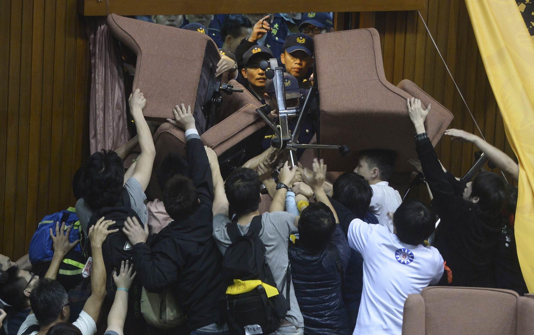 Estudantes taiwaneses que invadiram o parlamento em Taipei bloqueiam uma porta amontoando cadeiras para barrar a entrada da polícia. Os manifestantes invadiram o local para impedir a votação de um pacto de comércio com a China sem revisão item a item