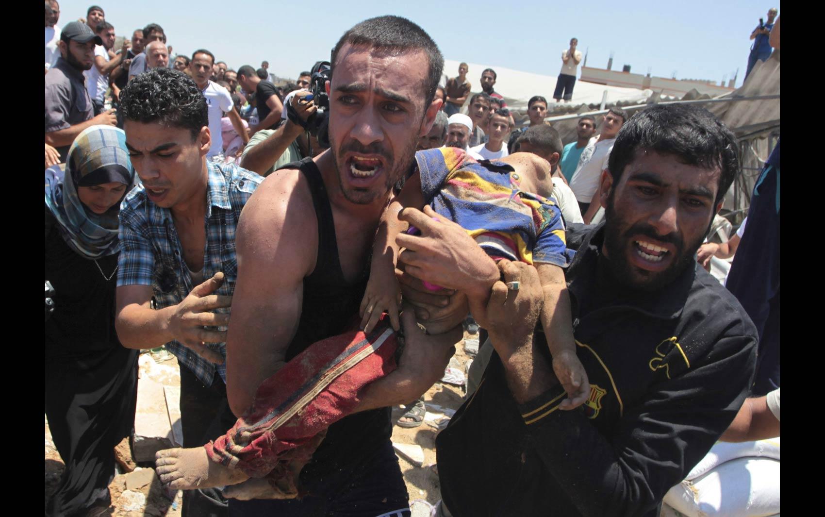 9/7 - Homens carregam o corpo de um menino palestino morto no que, segundo fontes de um hospital, foi um ataque aéreo israelense à casa de sua família na Cidade de Gaza
