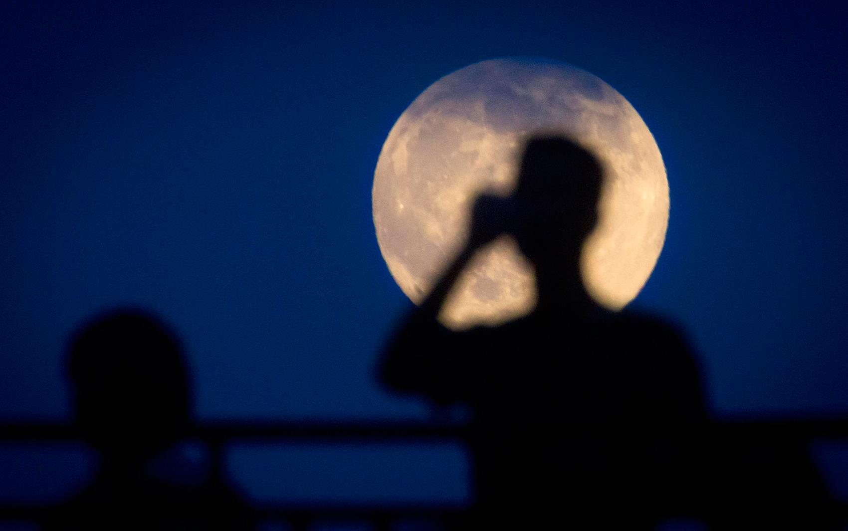 Homem fotografa a superlua em cima de ponte, em Manhattan, em Nova York, na madrugada desta sábado (12)