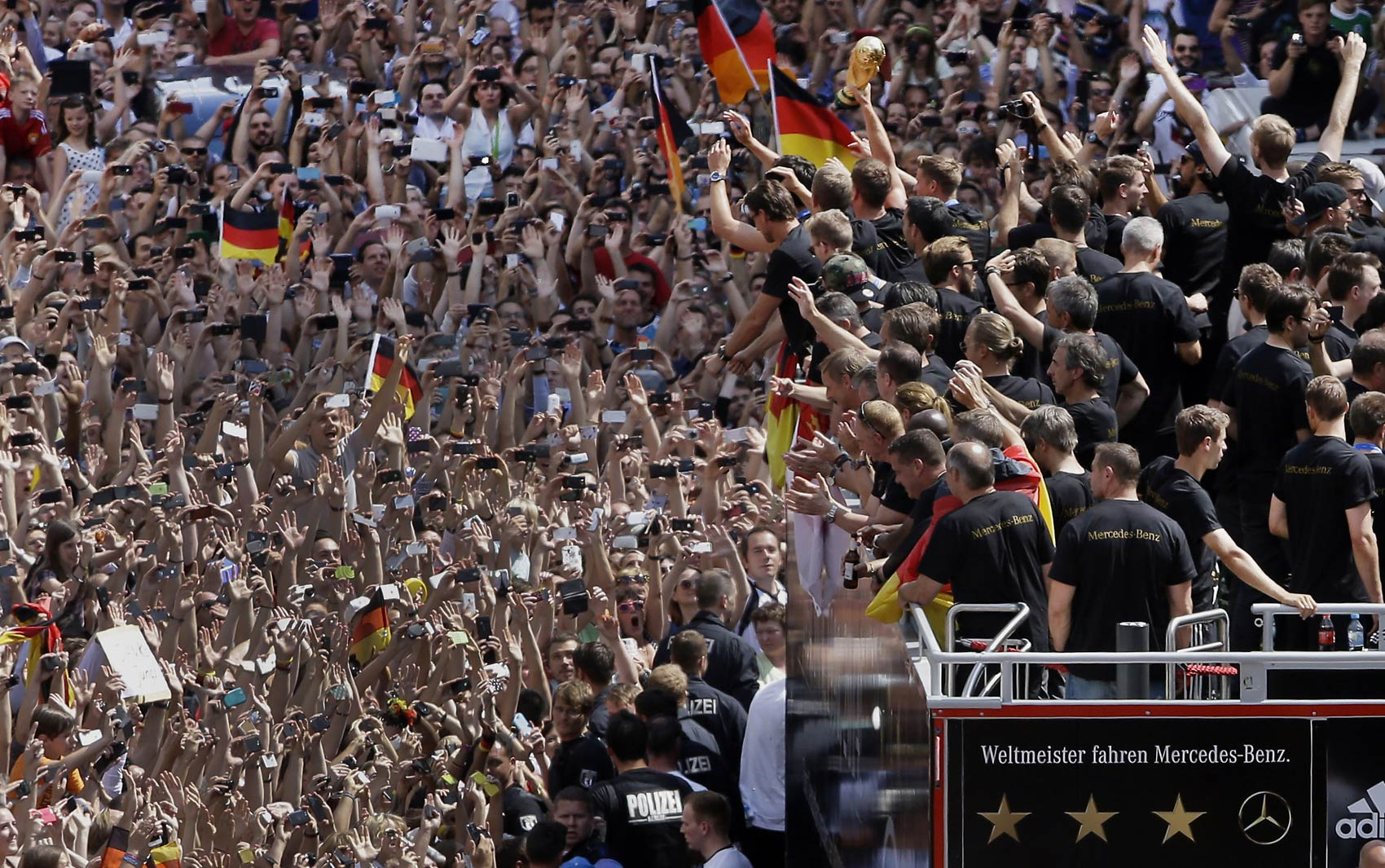 15/7 - Multidão recebe a seleção da Alemanha de volta a Berlim com a Taça do Mundo