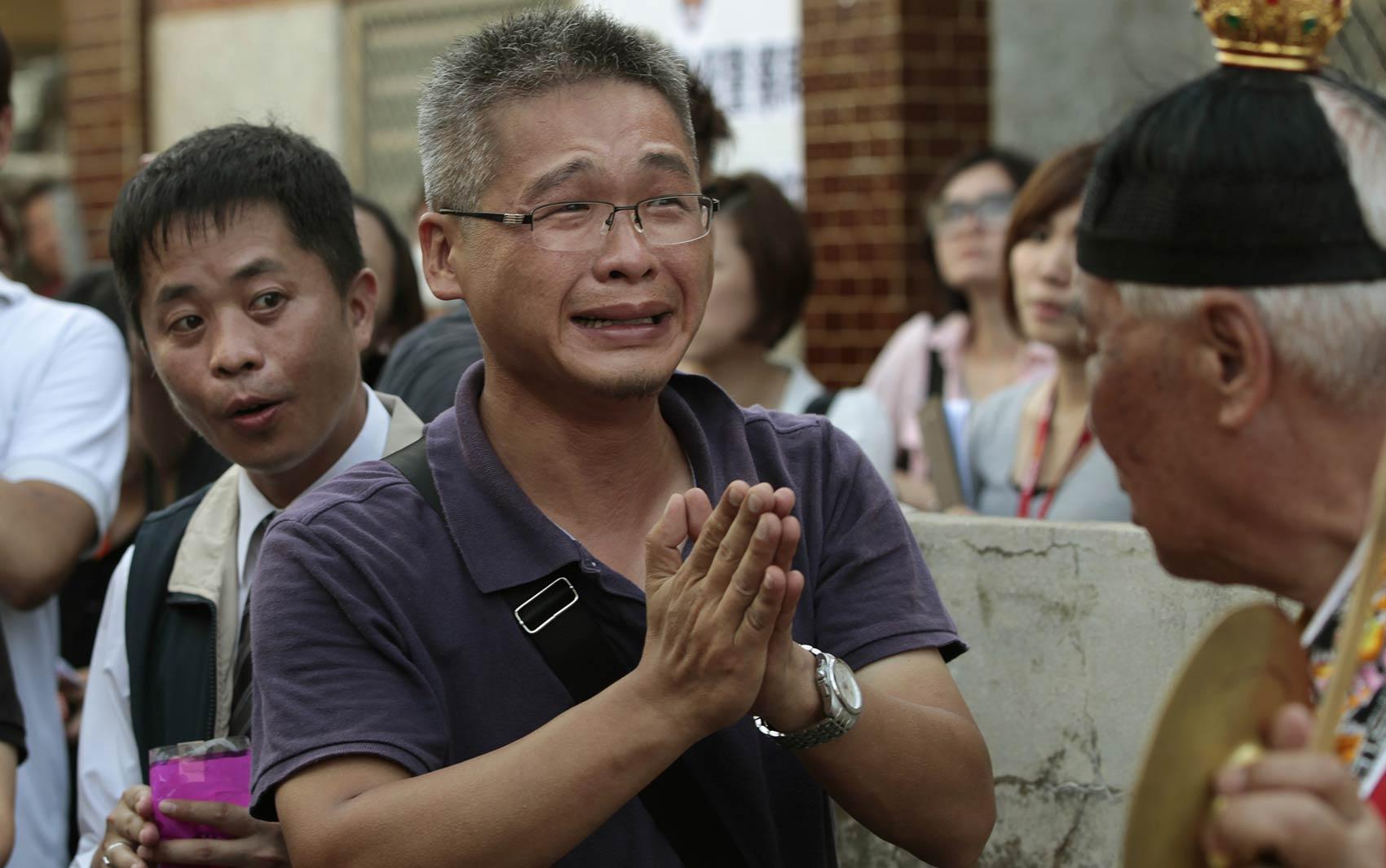 24/7 - Familiar de vítima morta no voo GE222 faz oração diante de altar montado no local do acidente na ilha de Penghu
