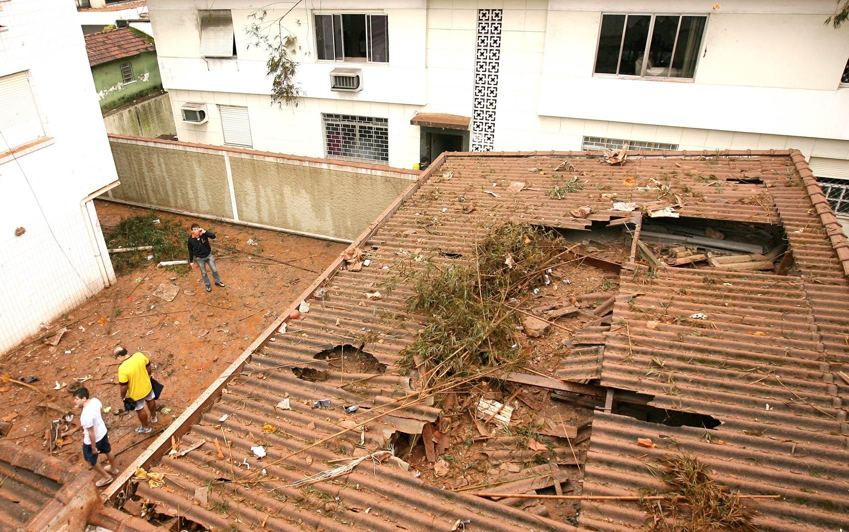 Pessoas observam destruição causada pela queda do avião em Santos