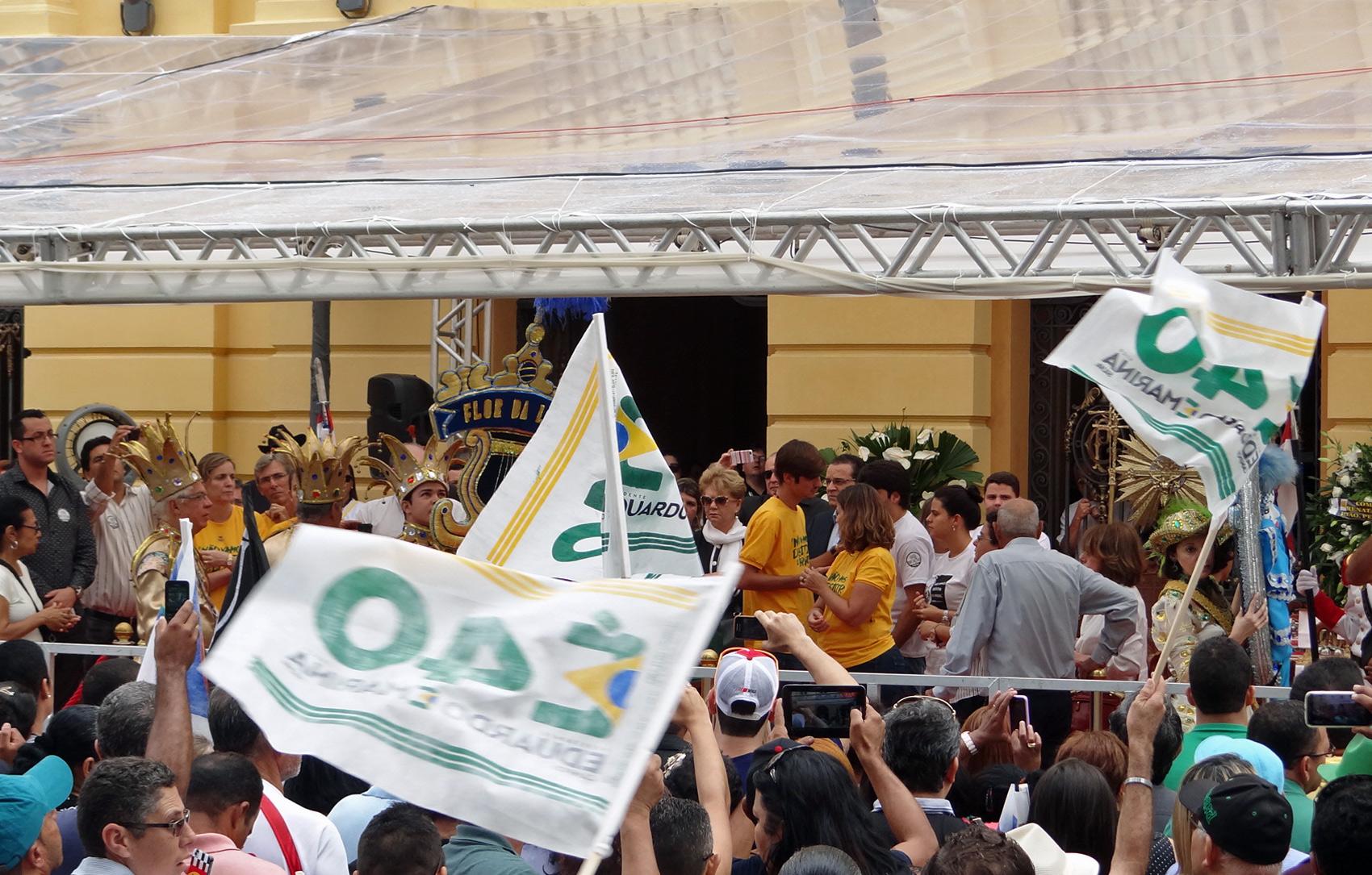 No entorno do Palácio, as pessoas carregam bandeiras e usam camisas para prestar homenagem a Campos