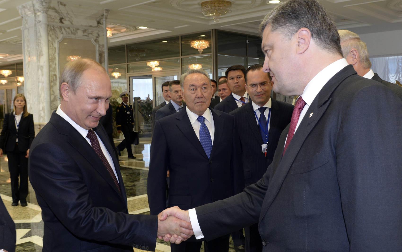 Os presidentes Vladimir Putin (esq.), da Rússia, e Petro Poroshenko (dir.) da Ucrânia, dão aperto de mão em Minsk, Belarus. Foi o primeiro encontro entre os dois desde junho para falar sobre a crise entre os dois países