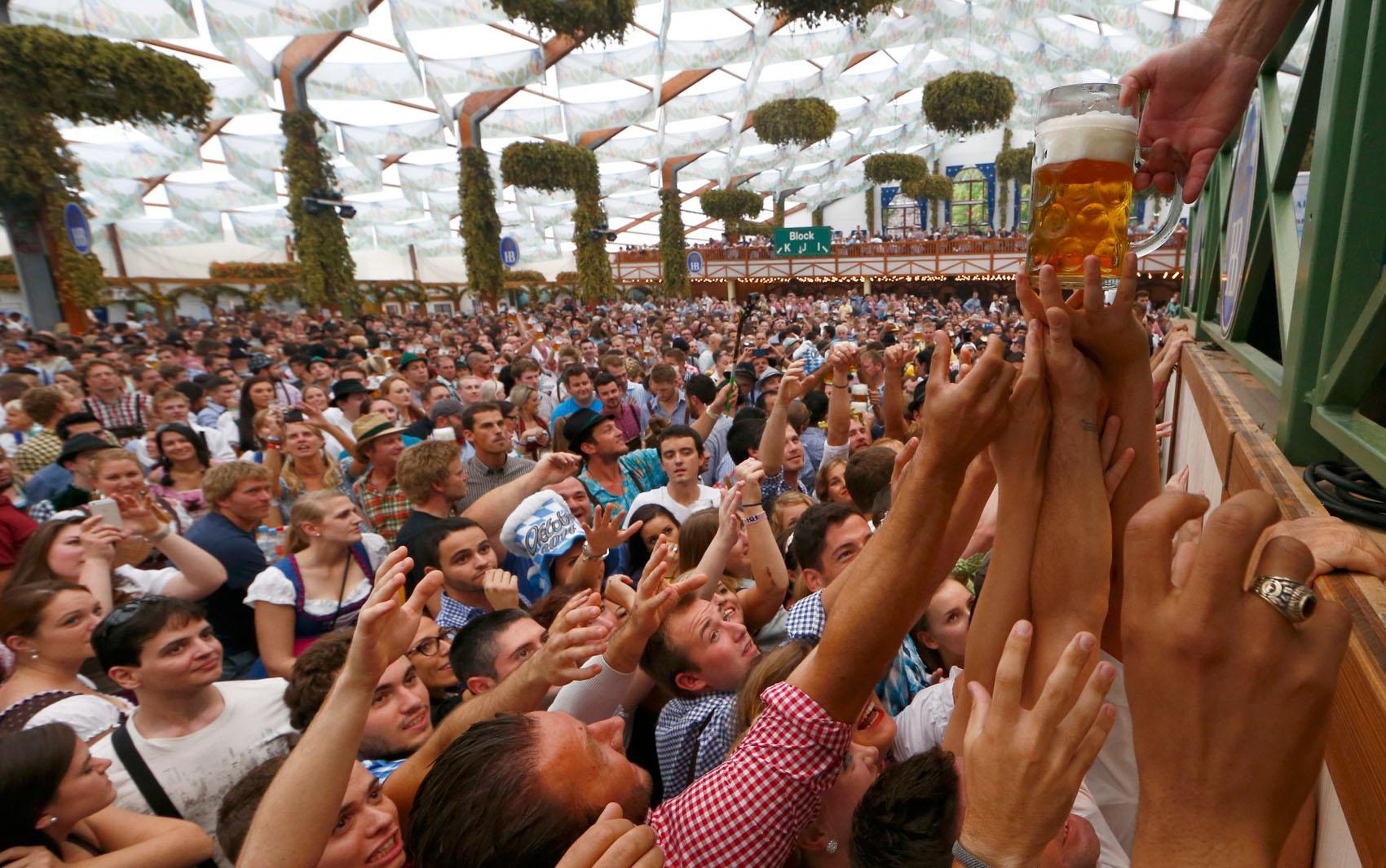 20/9 - Visitante se esticam e disputam um dos primeiros canecões de cerveja servidos após a abertura oficial da Oktoberfest. Realizado anualmente, o festival de cerveja atrai milhões de turistas à capital da Bavária durante duas semanas