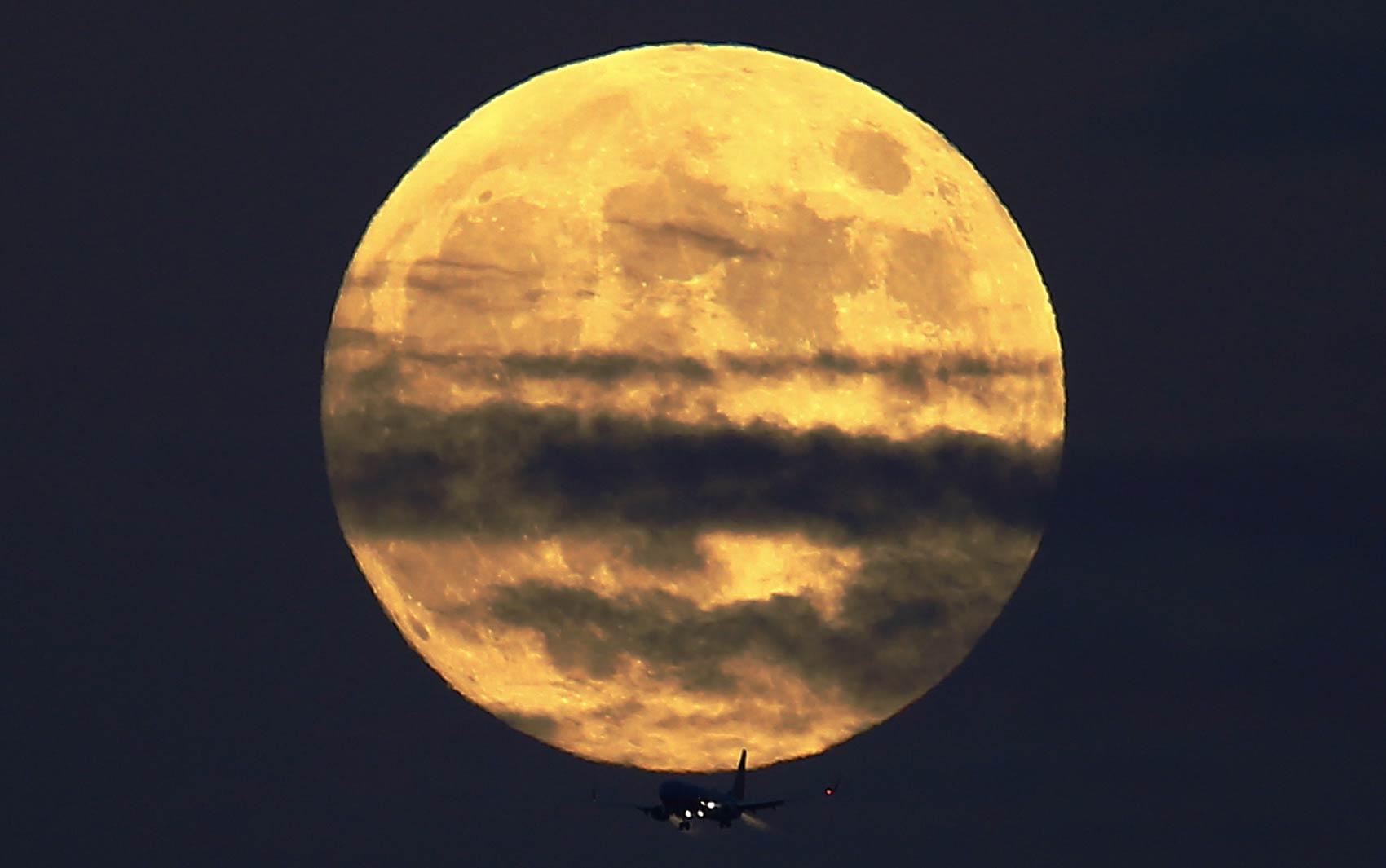 Avião comercial passa abaixo da 'Lua de sangue' antes de pousar no aeroporto de Lindberg Field em San Diego, na Califórnia (EUA). Fenômeno do eclipse lunar dá tom avermelhado à Lua
