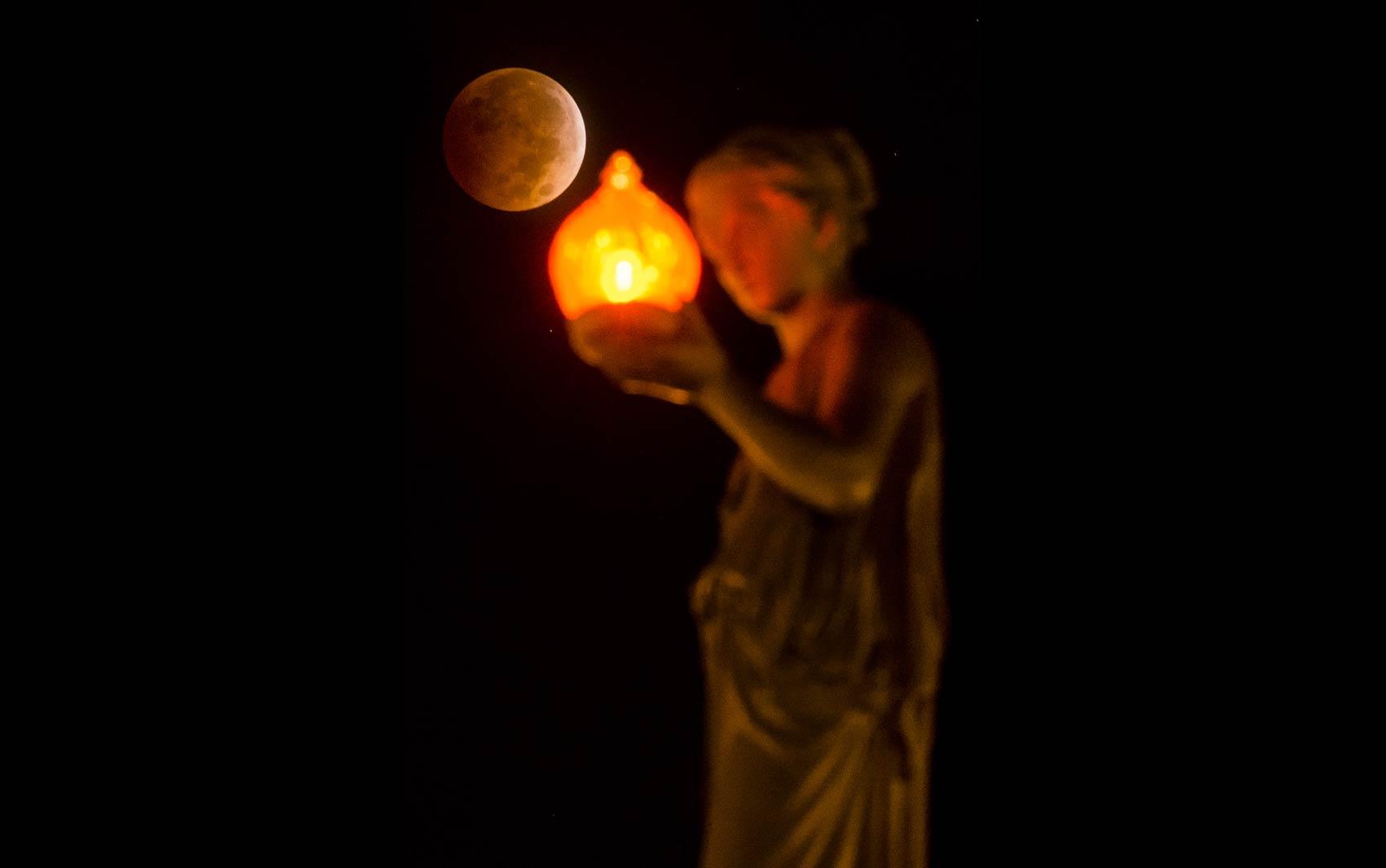 'Lua de sangue' é vista por trás de uma estátua no topo do Wheeler Town Clock em Manitou Springs, Colorado (EUA)