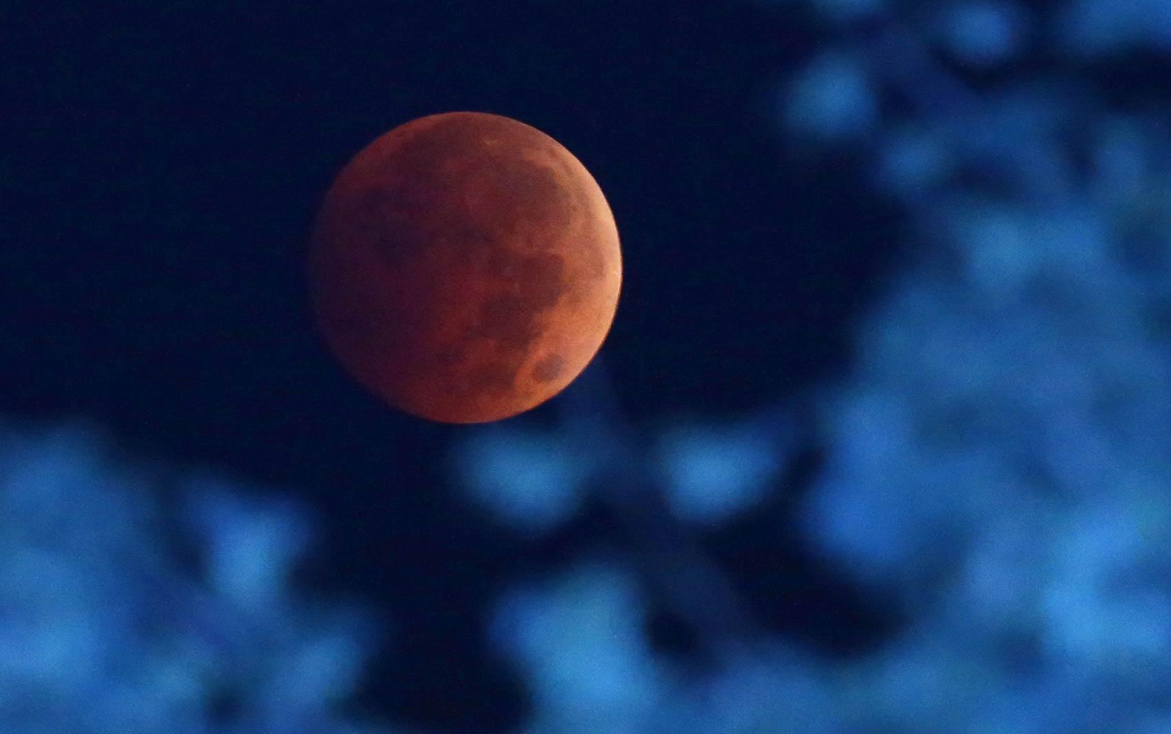 Passagem da luz do sol através da atmosfera terrestre faz com que a Lua ganhe tom avermelhado durante eclipse lunar visto de Milwaukee, nos EUA. O fenômeno é conhecido como 'Lua de sangue'