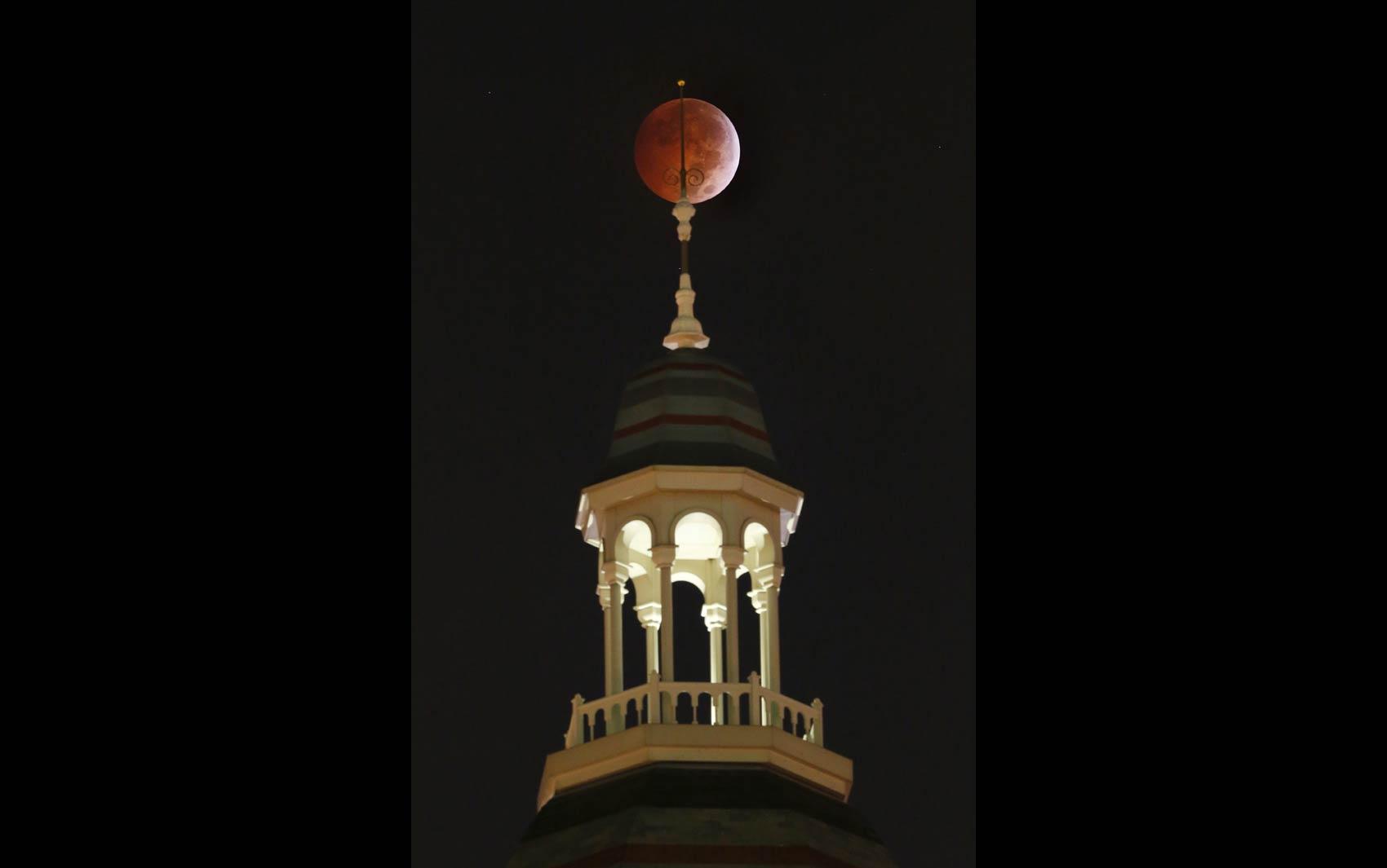 'Lua de sangue' é vista por trás de uma estátua no topo do antigo Tribunal do Condado de Dallas, nos EUA