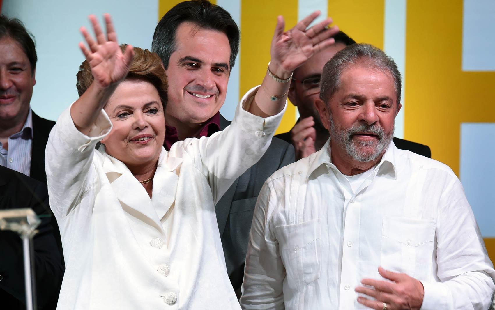 Dilma Rousseff acena para apoiadores celebrando sua reeleição ao lado do ex-presidente Lula em Brasília
