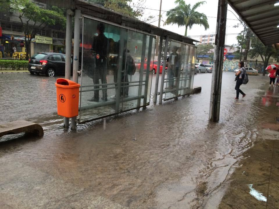 Pessoas subiram nos bancos de um ponto de ônibus para se protegerem da chuva, em Jardim Camburi