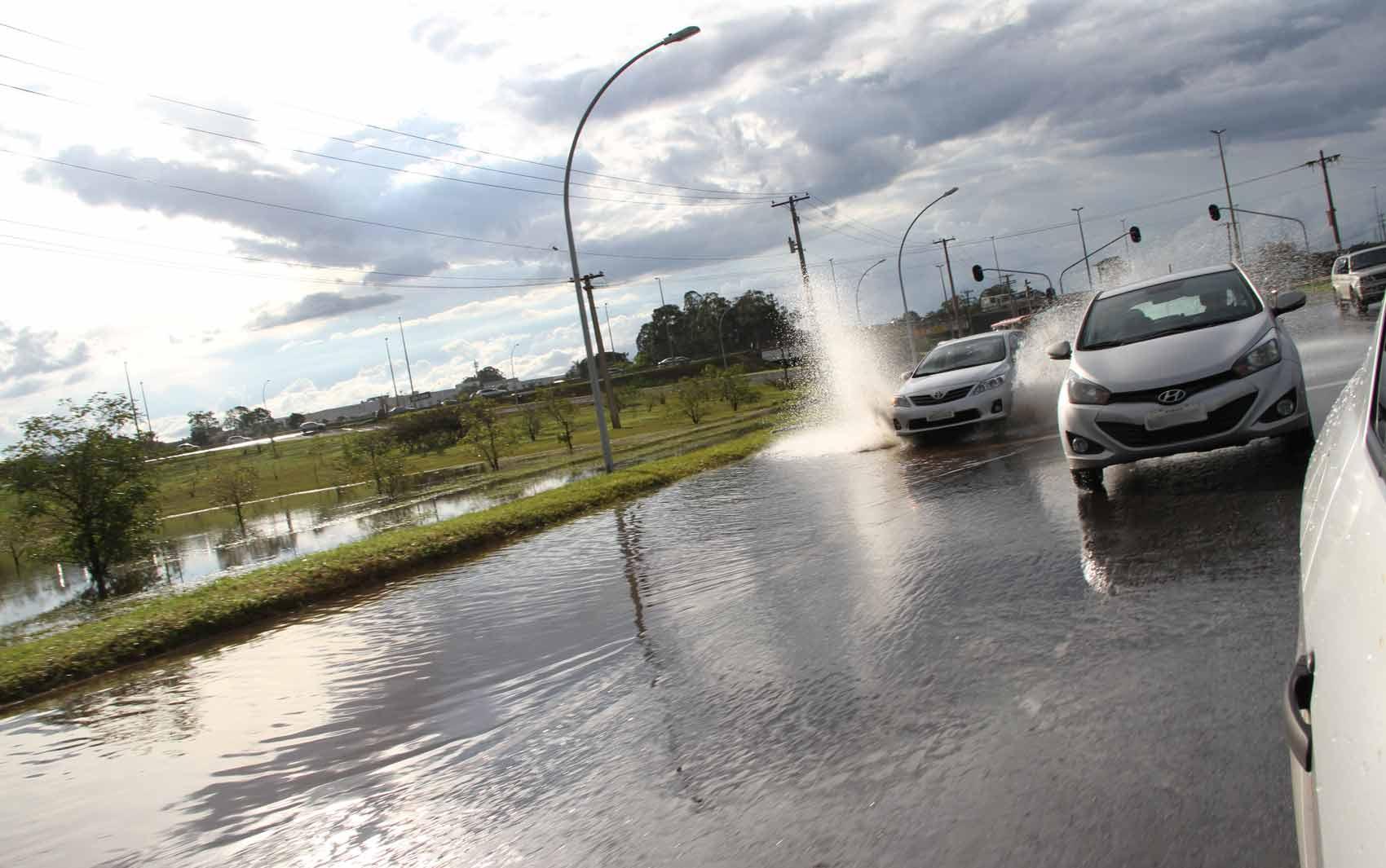 Carros passam por via alagada na região central de Brasília