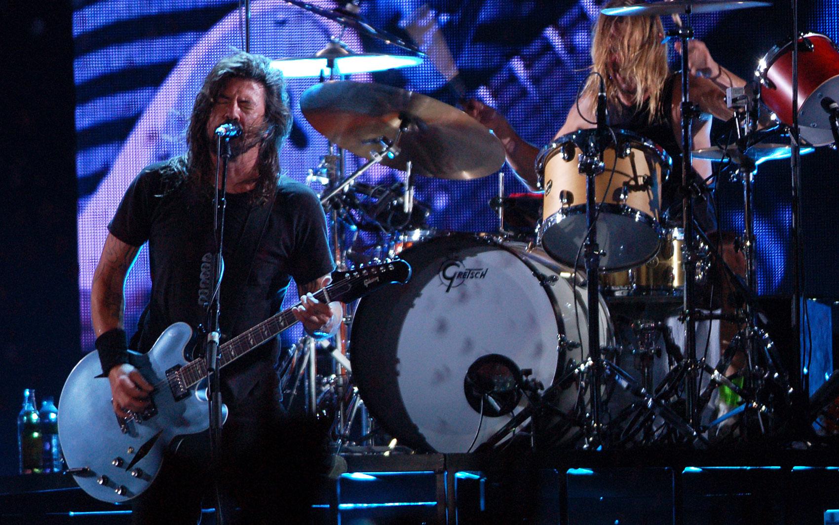 Com o baterista Taylor Hawkings ao fundo, Dave Grohl comanda o público do Foo Fighters durante show da banda no Estádio do Morumbi, em São Paulo