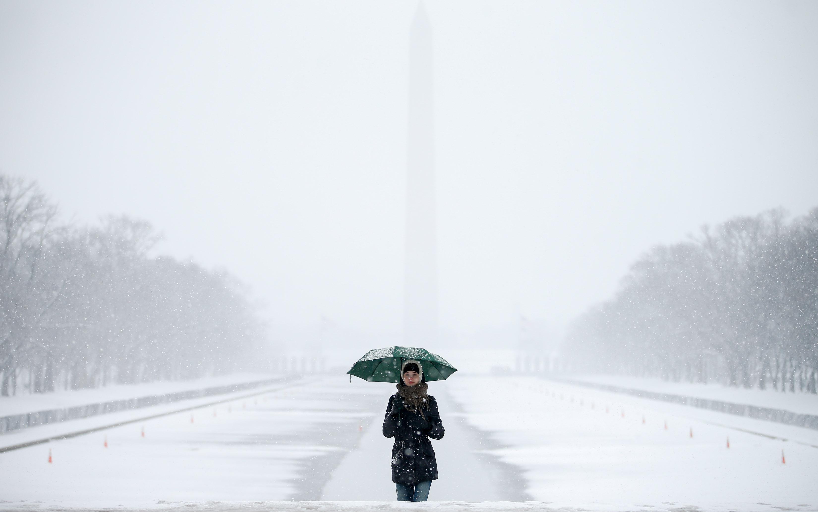 O monumento de Washington e o espelho d'água são vistos atrás de Claudia Marusanici, turista da Romênia, que caminha em direção ao Memorial do presidente americano Lincoln na capital americana