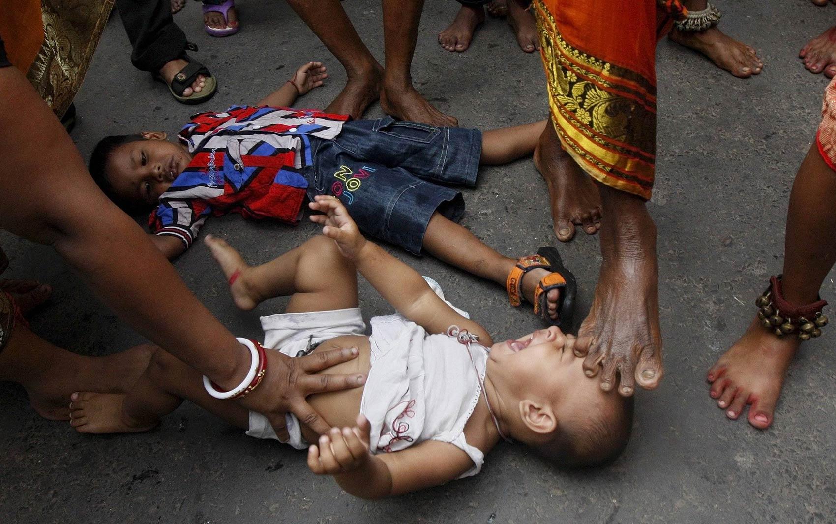15/4 - Homem hindu considerado santo coloca o pé sobre a cabeça de bebê que chora no chão durante procissão no festival Shiva Gajan, em Kolkata, na Índia. Os fiéis acreditam que o tradicional ritual abençoa as crianças, provendo saúde e prosperidade