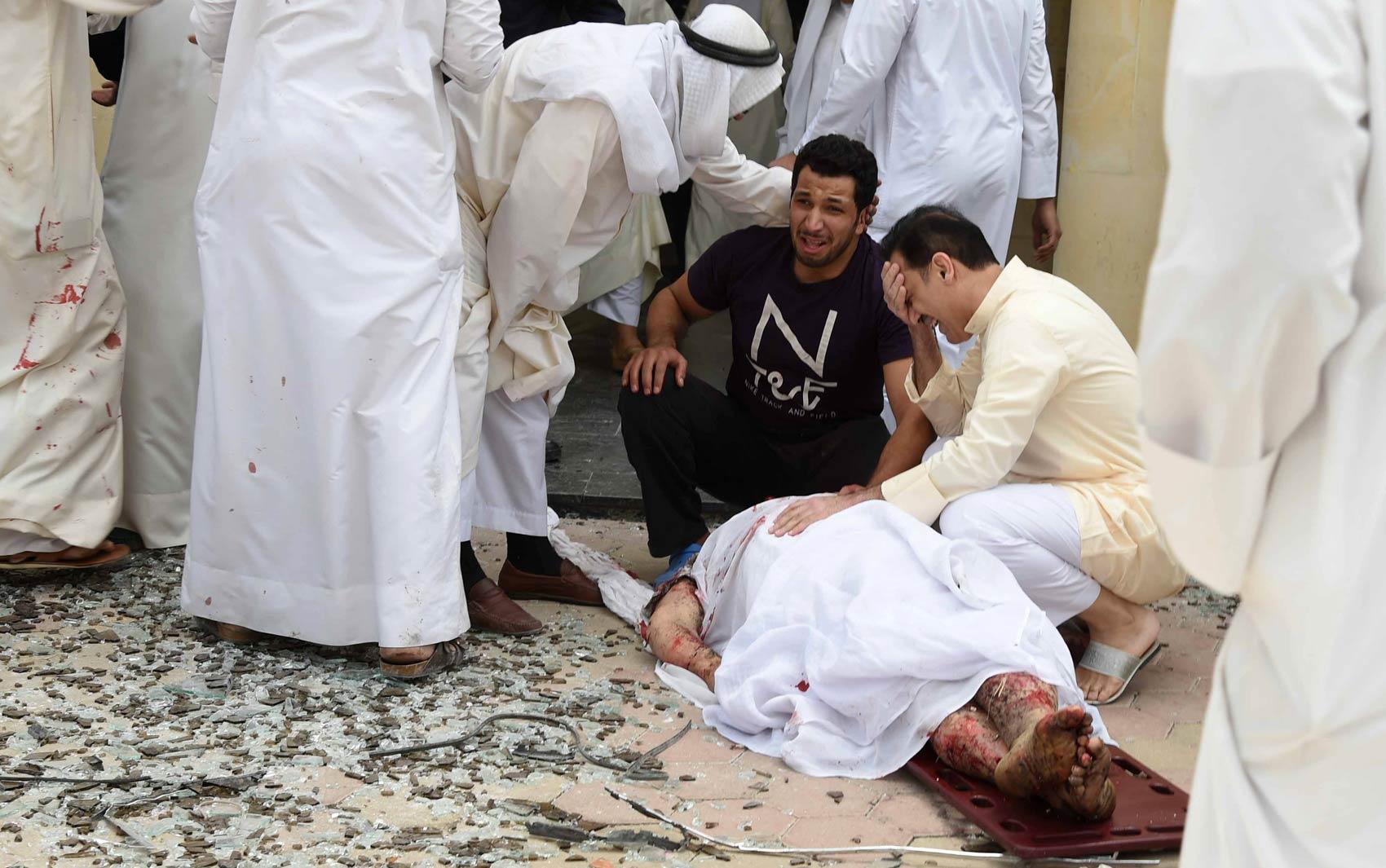 KUWAIT: Homens reagem diante do corpo de uma vítima do ataque suicida a bomba em uma mesquita da Cidade do Kuwait