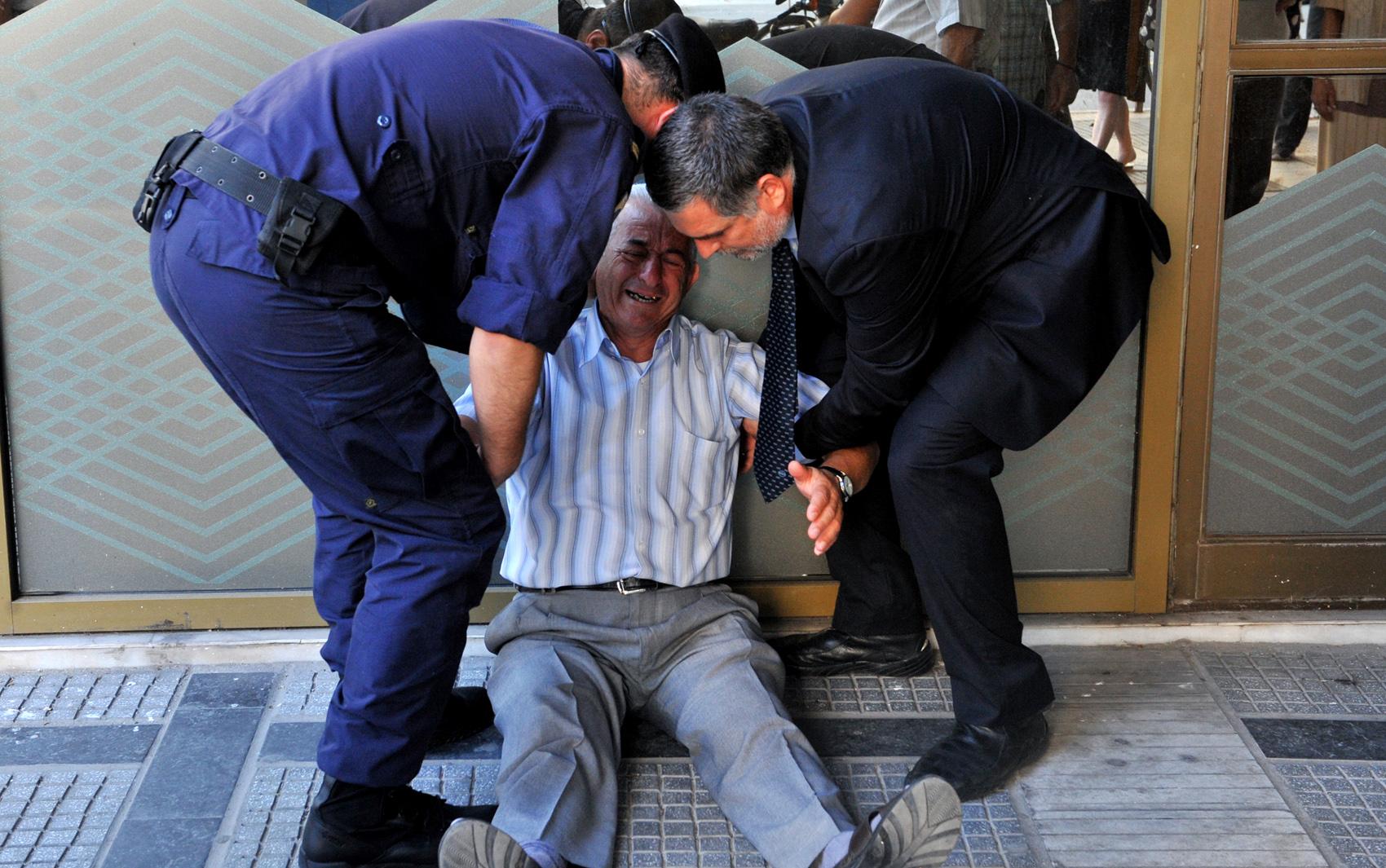 Idoso chora e é amparado em frente a agência bancária em Thessaloniki; saques foram limitados pelo governo e cartão de débito não é comum entre aposentados