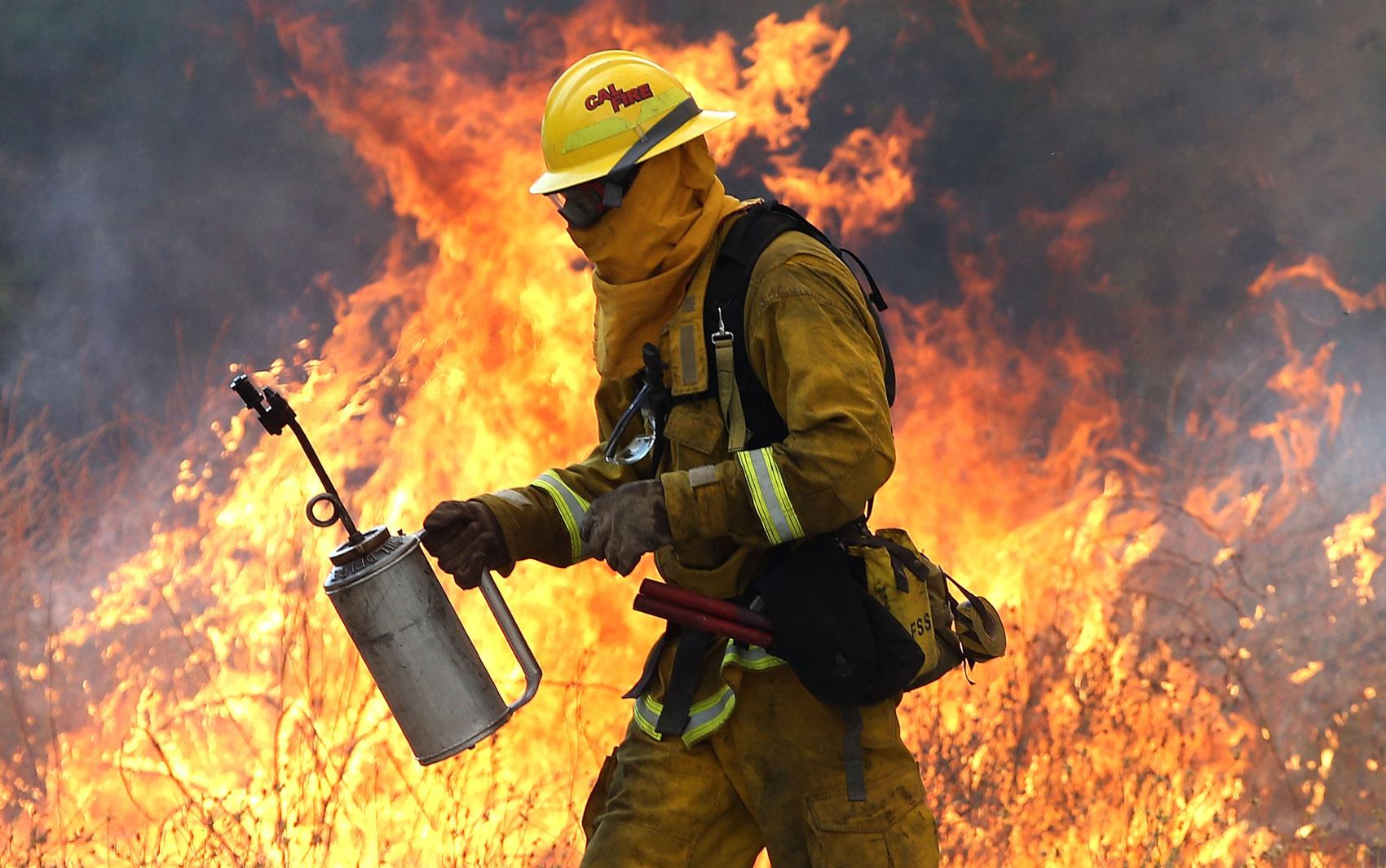 Um bombeiro se afasta de chamas durante ação perto de Clearlake, na California. Cerca de 3 mil bombeiros estão lutando contra o fogo que queimou mais de 24 mil hectares e forçou a evacuação de 12 mil moradores do Condado de Lake
