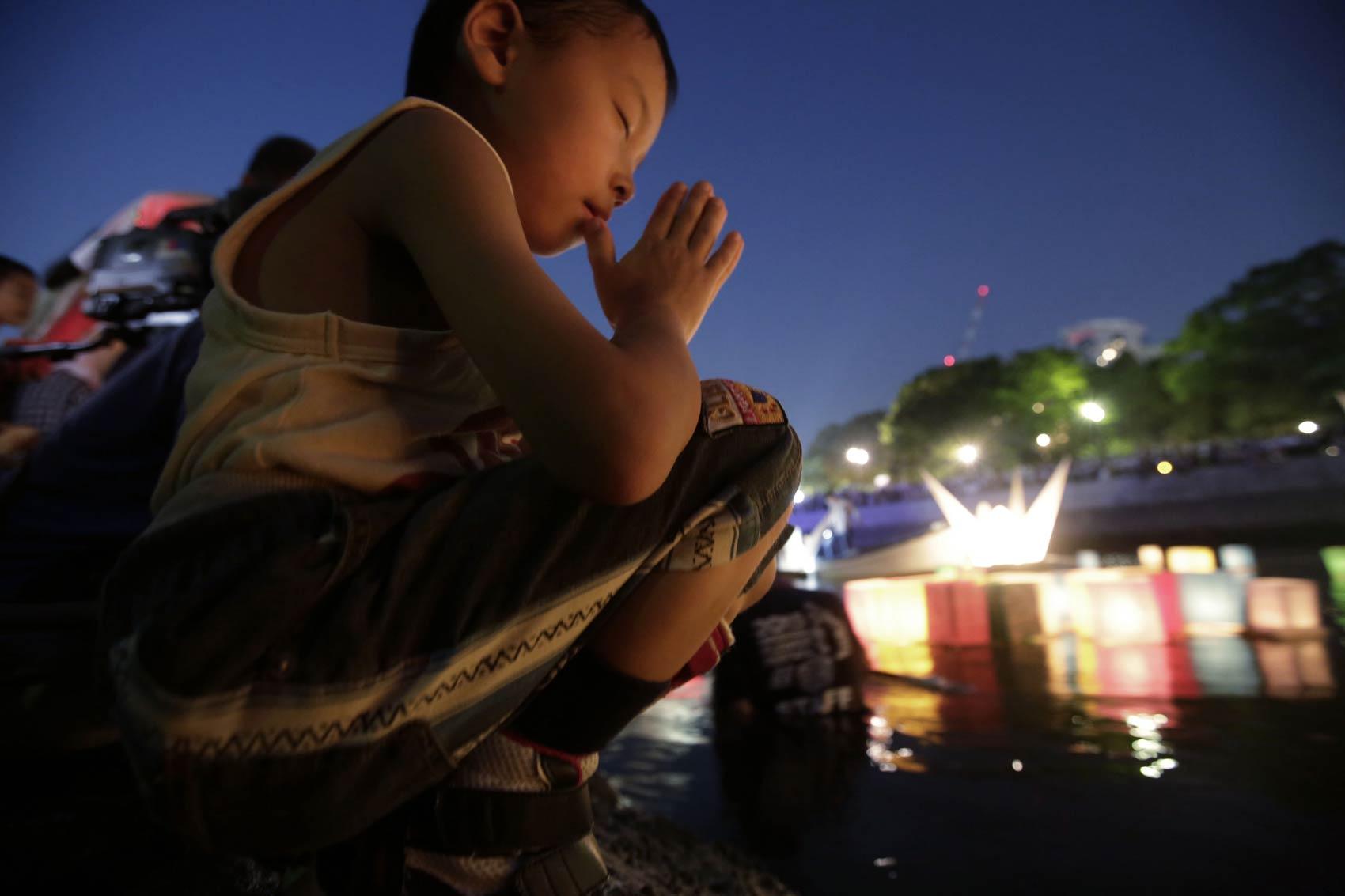 Menino faz oração após colocar uma lanterna japonesa de papel no rio Motoyasu, diante do Domo da Bomba Atômica em Hiroshima, durante memorial dos 70 anos da explosão da bomba que deixou 140 mil mortos na cidade ao fim da II Guerra Mundial